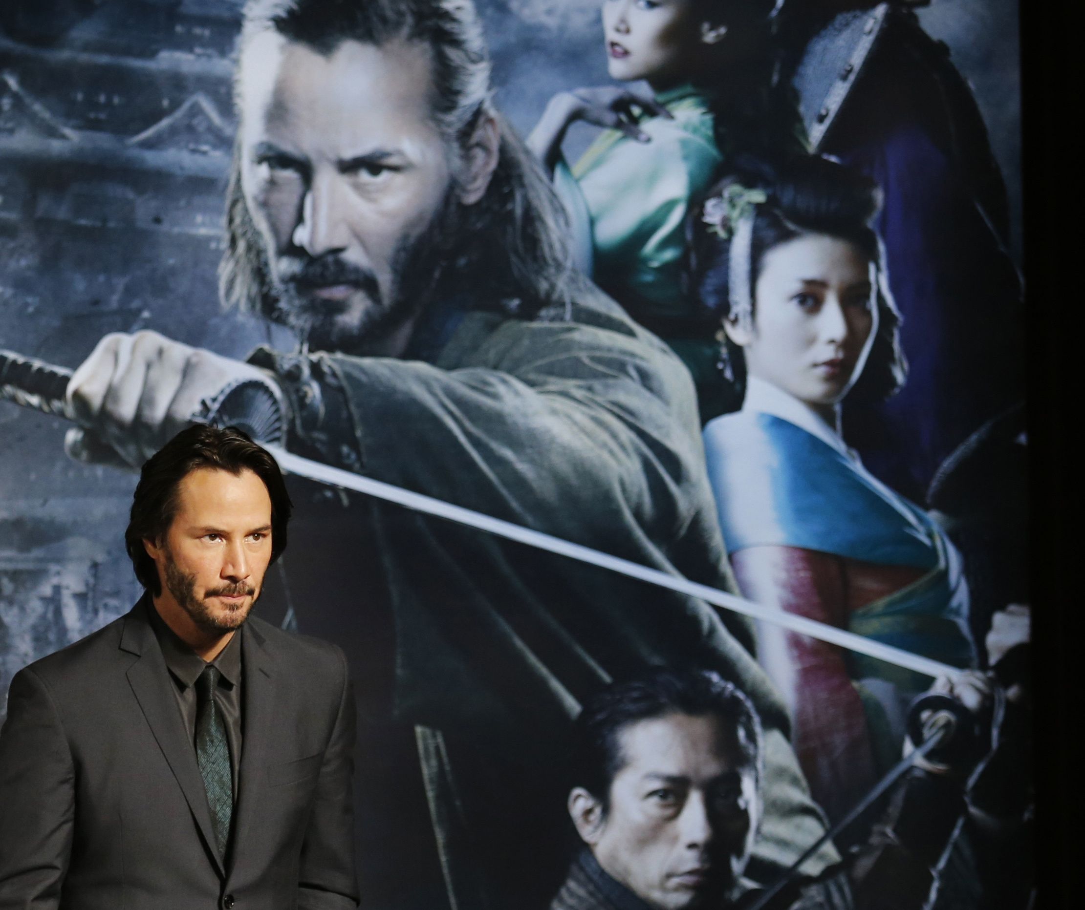 "Actor Keanu Reeves stands before a poster for ""47 Ronin"" during a press conference to promote the 3-D film in Tokyo on Monday."