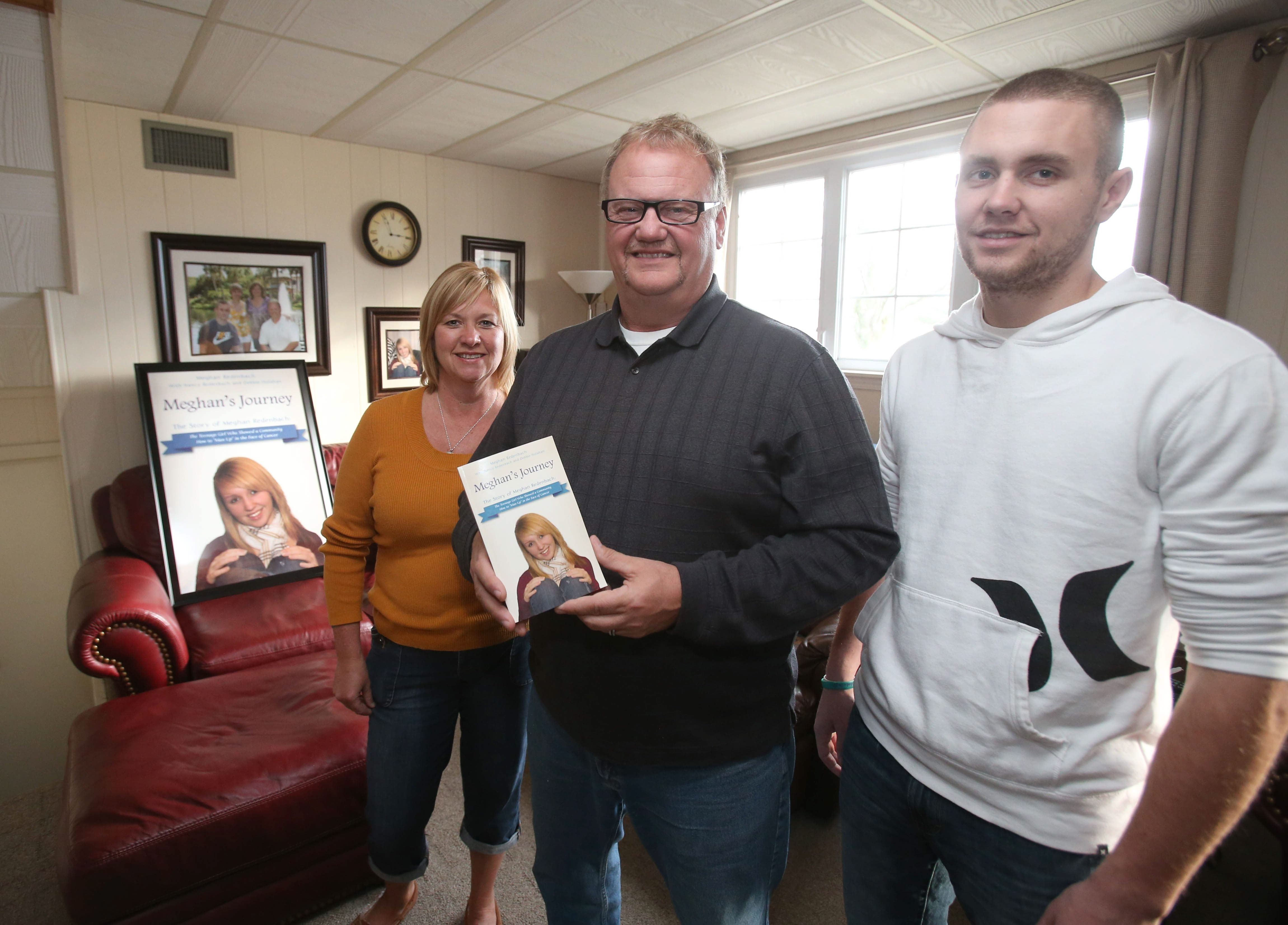 """Meghan Redenbach's father, Michael, joined by wife Nancy and son Nick, 23, shows a copy of new book """"Meghan's Journey,"""" the story of """"The Teenage Girl Who Showed a Community How to 'Man Up' in the Face of Cancer."""" Meghan, 15, died in 2010"""