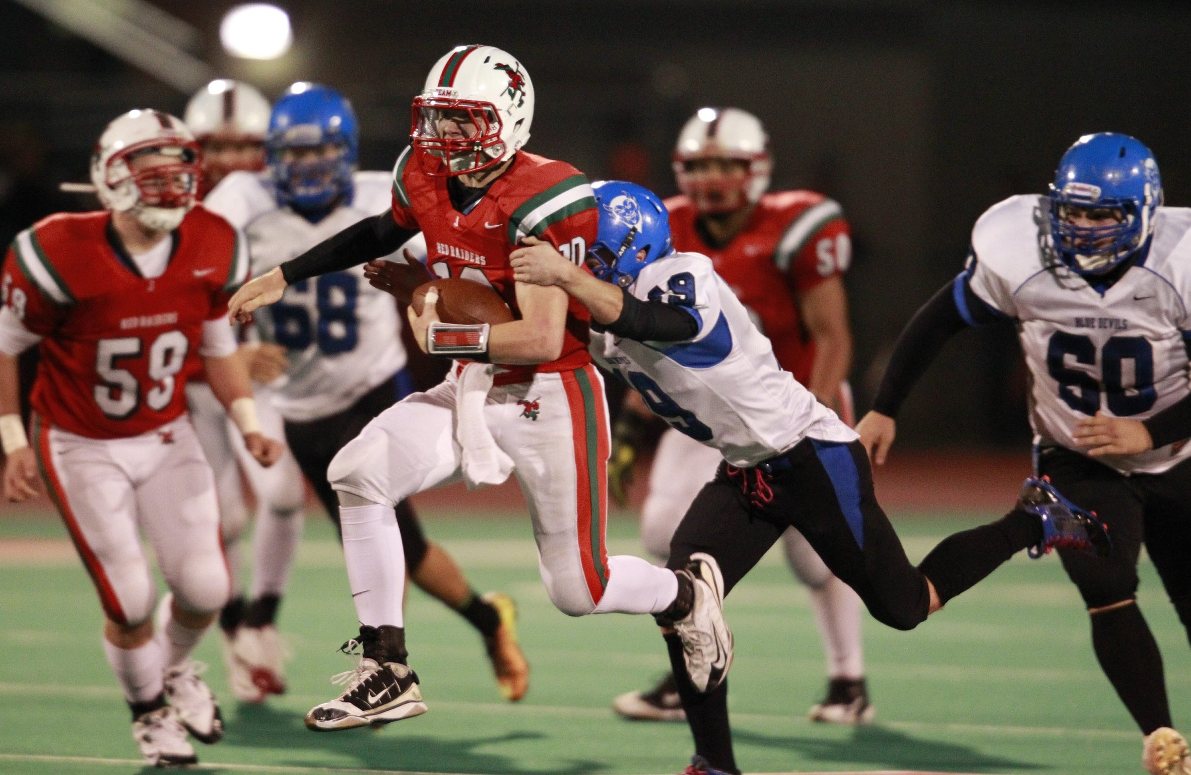 Jamestown quarterback Jake Sisson jumps as he runs against Kenmore West on Friday night during the Red Raiders' rout.