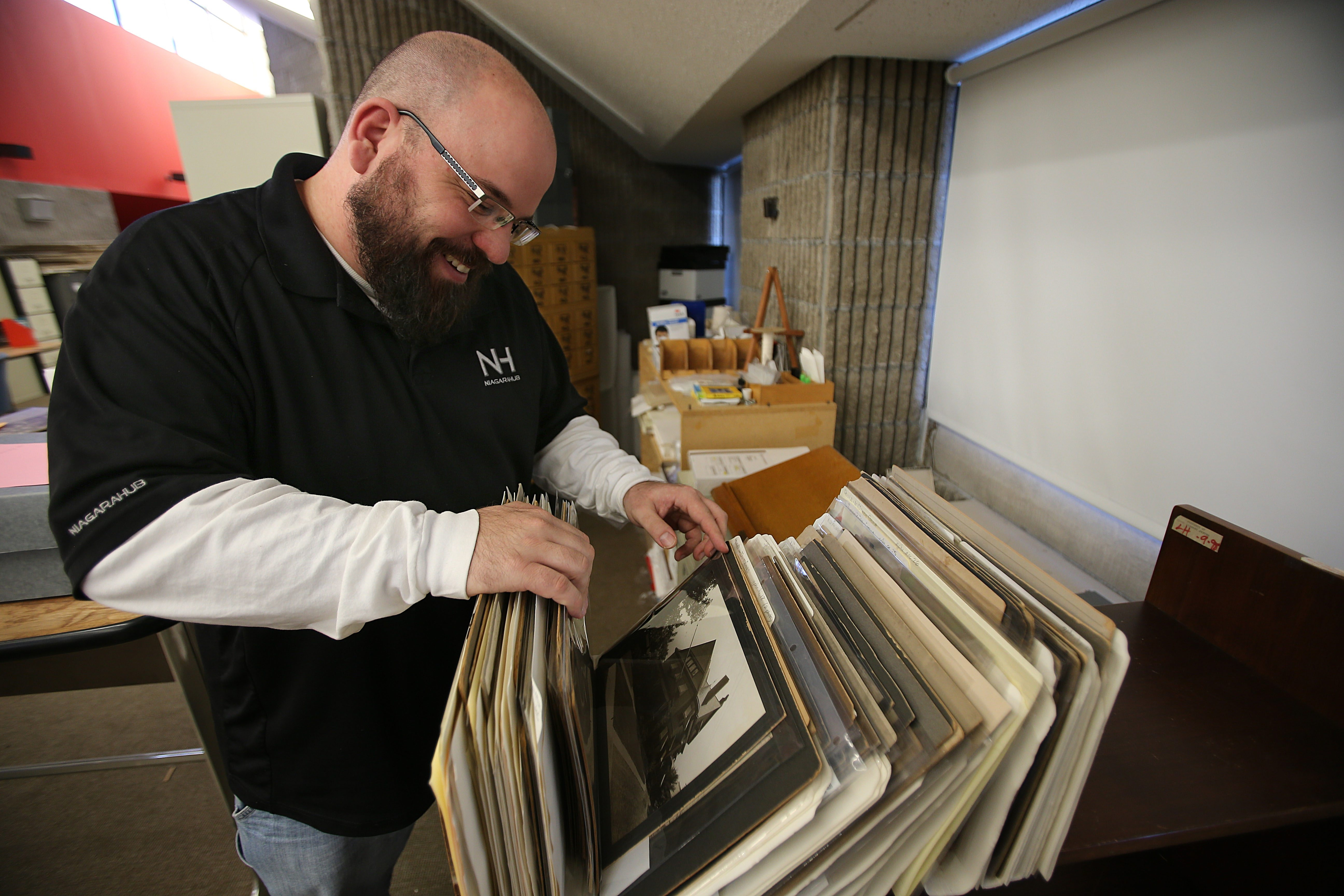 Niagara Falls City Historian Christopher Stoianoff looks through piles of old photos waiting to be scanned into a computer at the main branch of the Niagara Falls Public Library. The photos will be available online.