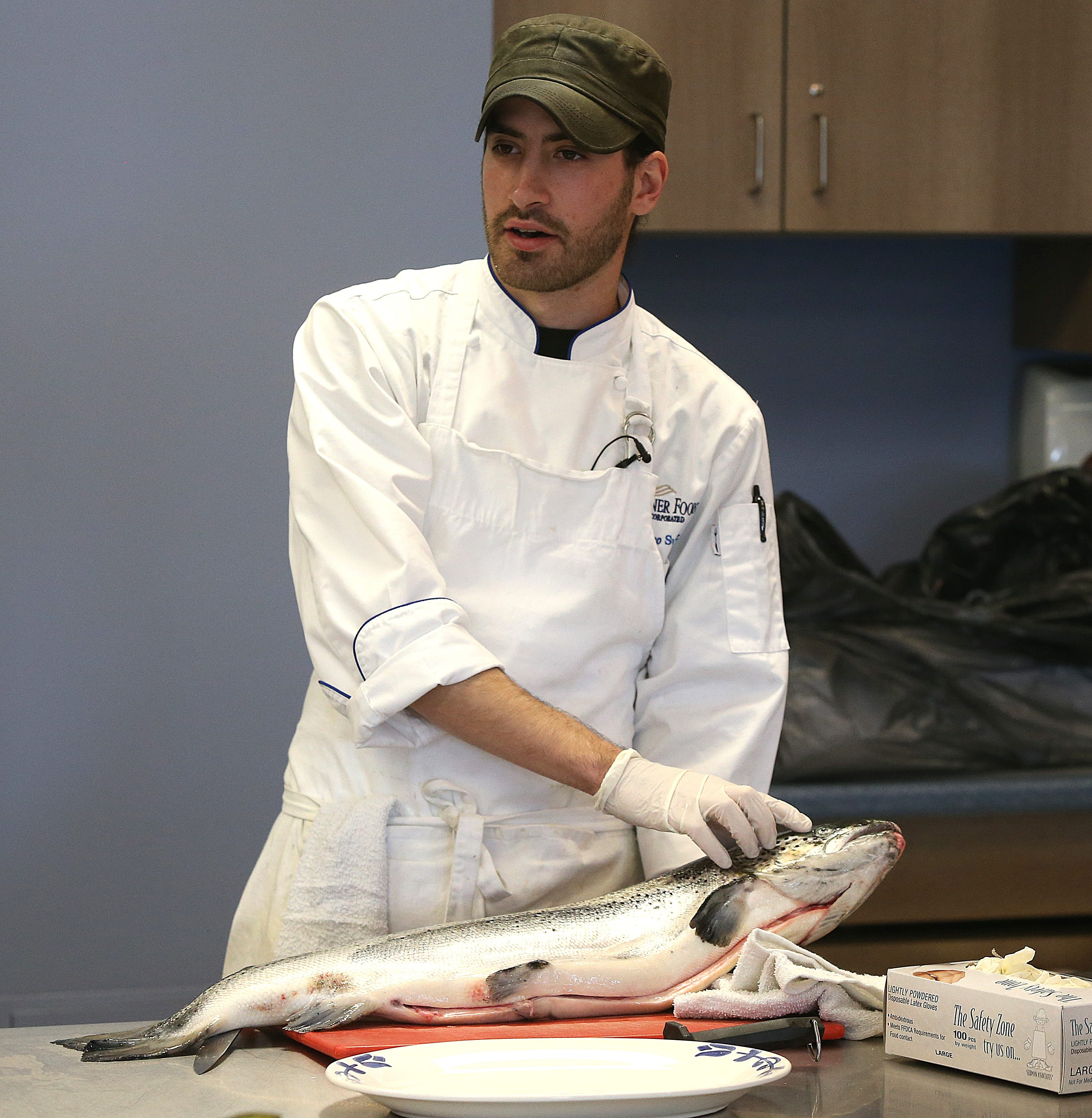 Chef Marco Suarez teaches students how to clean and fillet a fish at Frontier High School on Wednesday.
