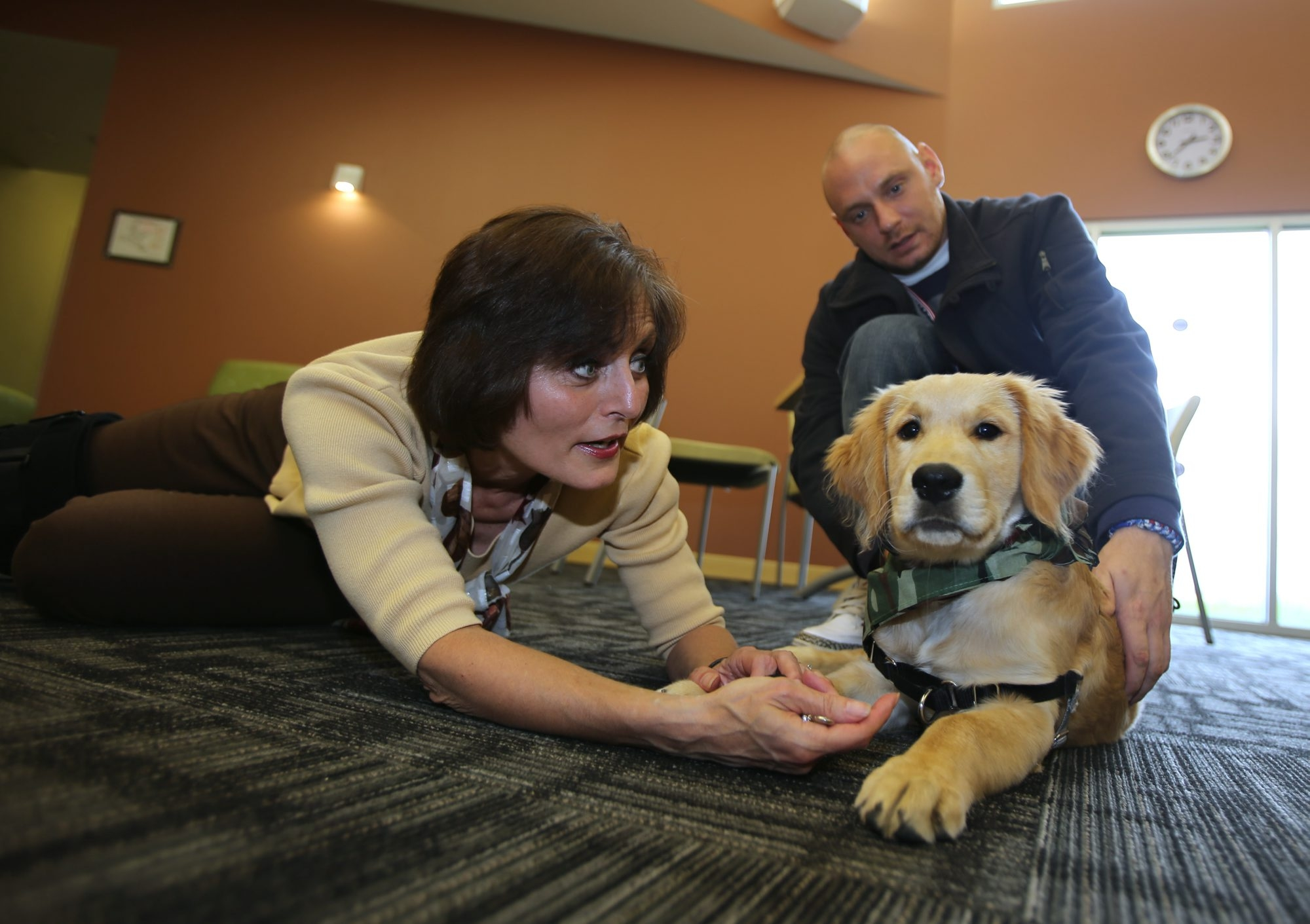 """Wellness coordinator Diane Bly and her dog, Dakota, interact with client Michael Girard, of Buffalo, at """"Freedom Village,"""" where veterans are offered inpatient services."""