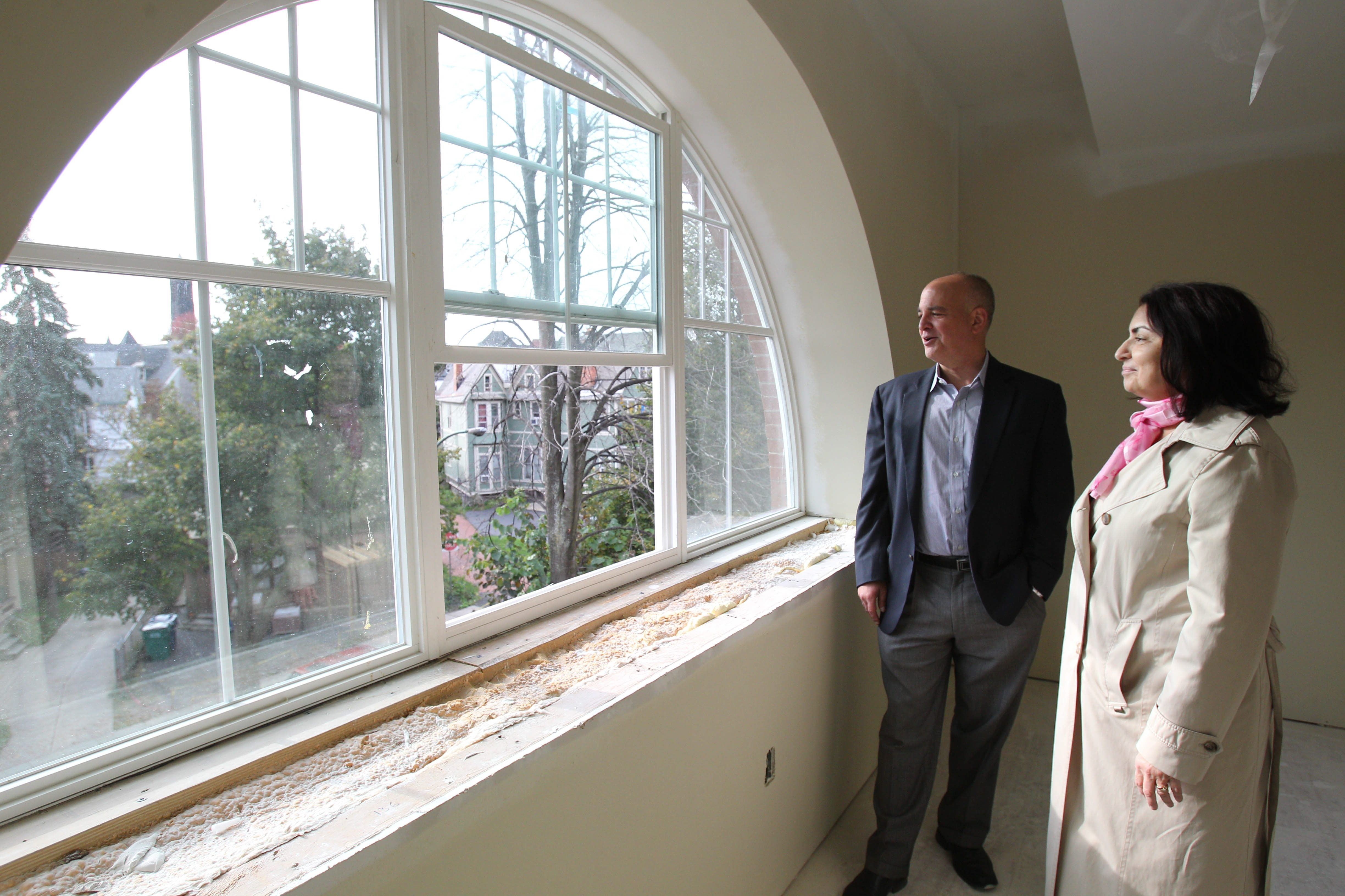 Developer Sam Savarino and Linda Chiarenza, executive director of Westside Neighborhood Housing Services, the not-for-profit sponsor of the site, tour the new apartments that will be completed soon at the former White's Livery & Boarding Stables on Jersey Street.