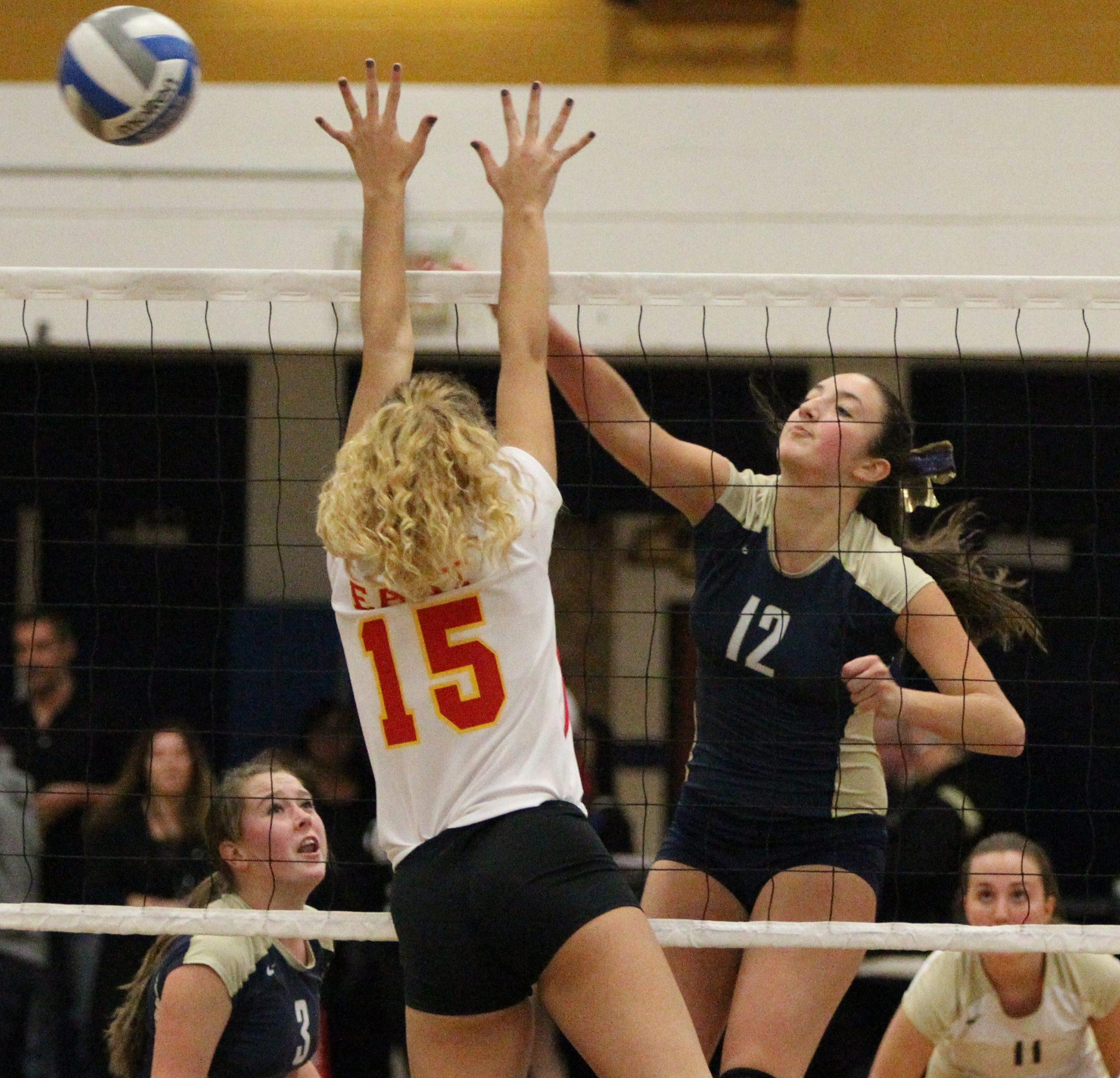 Sweet Home's Rachel Reusch spikes the ball over Williamsville East's Lexi Novak during Tuesday's Section VI Class A final.  {Photo by James P. McCoy / Buffalo News}