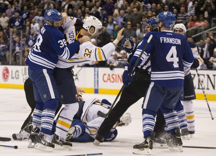 Toronto Maple Leafs Frazer McLaren (38) grabs John Scott (32) of the Buffalo Sabres as players from both sides grapple during the third period Saturday night. (Associated Press)