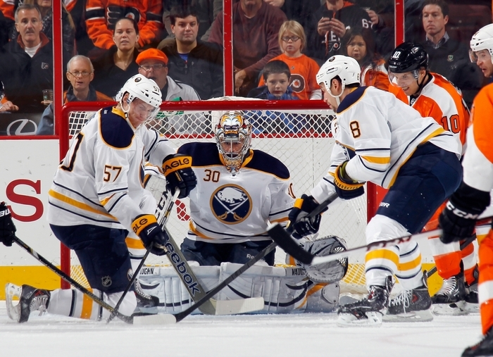 Tyler Myers, left, and Cody McCormick (8) keep the shot lane clear for Ryan Miller to make one of his 42 saves. (Getty Images)
