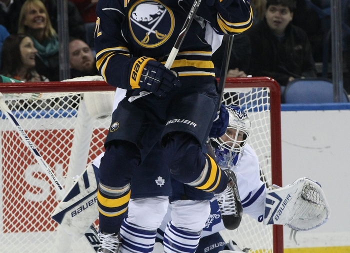 Sabres center Luke Adam works the crease against Maple Leafs goalie James Reimer in the first period at the First Niagara Center. (James P. McCoy/Buffalo News)