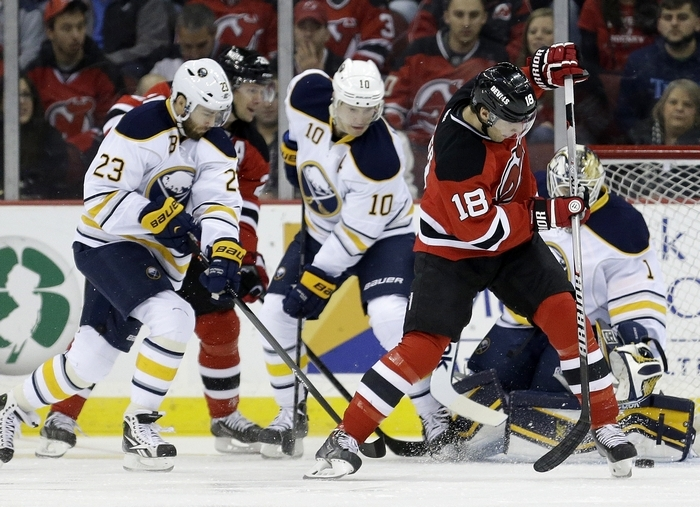 Devils winger Steve Bernier tries to muster a shot against Sabres goalie Jhonas Enroth as Buffalo's Ville Leino (23) and Christian Ehrhoff defend. (Associated Press)