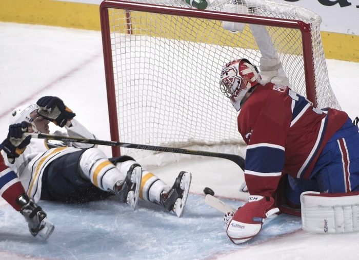 Buffalo's Zemgus Girgensons (28) slides by Montreal Canadiens goalie Carey Price as he scores the Sabres' final goal of the game early in the third period. (The Associated Press)