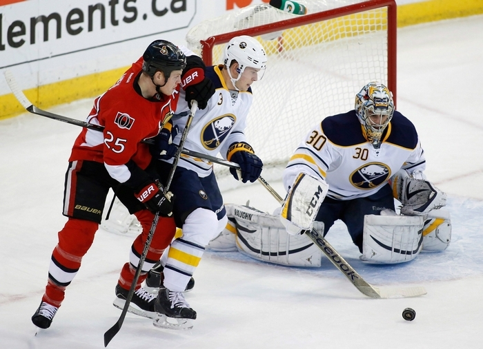 Ottawa Senators Chris Neil, left, and the Buffalo Sabres Mark Pysyk struggle for the puck in front of Sabres goaltender Ryan Miller during the first period of an NHL hockey game, Thursday, Dec. 12, 2013 in Ottawa, Ontario. (AP Photo/The Canadian Press, Patrick Doyle)