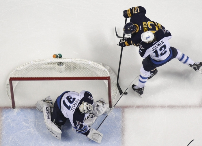 Buffalo's Kevin Porter (12) tries to slide the puck past Winnipeg Jets goaltender Ondrej Pavelec and defenseman Olli Jokinen (12) during first-period action at the First Niagara Center on Tuesday. (Harry Scull Jr./Buffalo News)