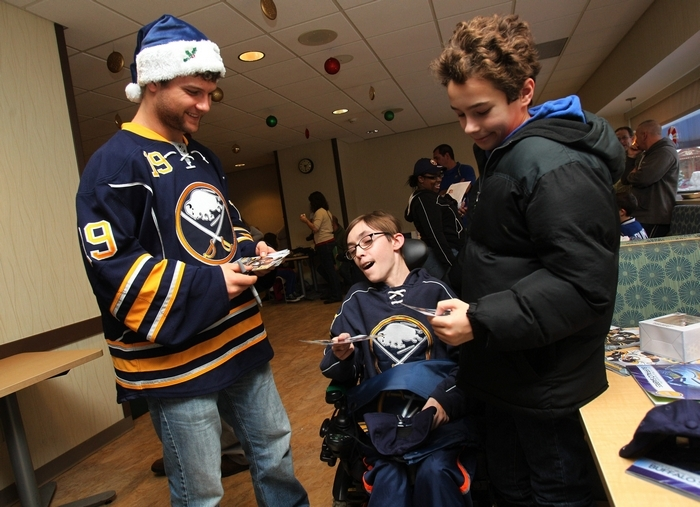 Cody Hodgson gives an autographed photo to Tony Izzo, center, of East Aurora and his brother Matthew, 11, at Women & Children's Hospital. (Sharon Cantillon/Buffalo News)