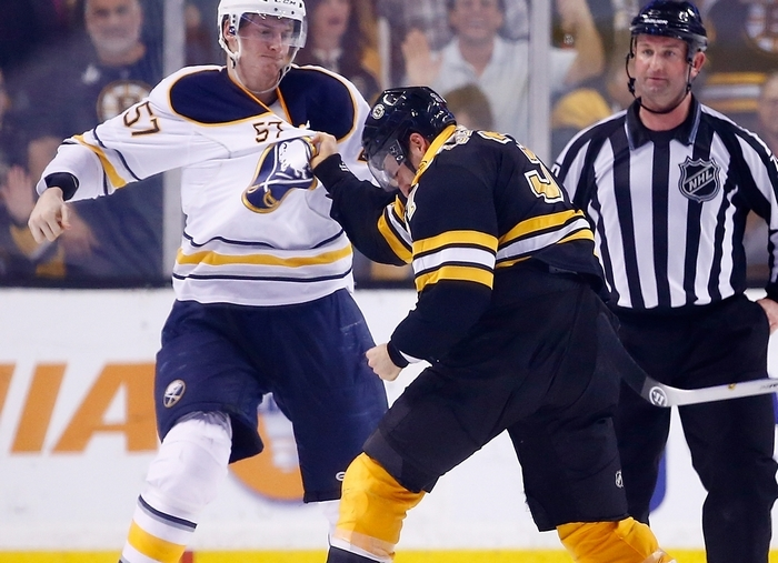 The Sabres' Tyler Myers looks to unload on Boston's Patrice Bergeron during a fight Saturday at TD Garden. (Getty Images)