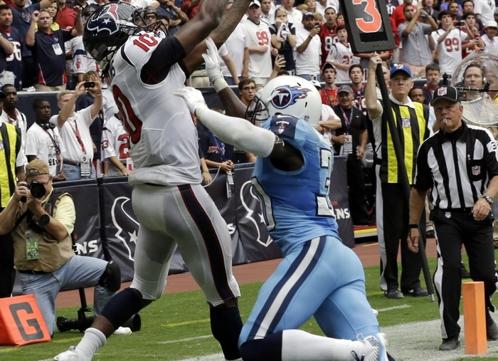 The Texans' DeAndre Hopkins catches the winning touchdown over Tennessee's Jason McCourty during overtime in Sunday's game at Reliant Stadium in Houston. (Associated Press)