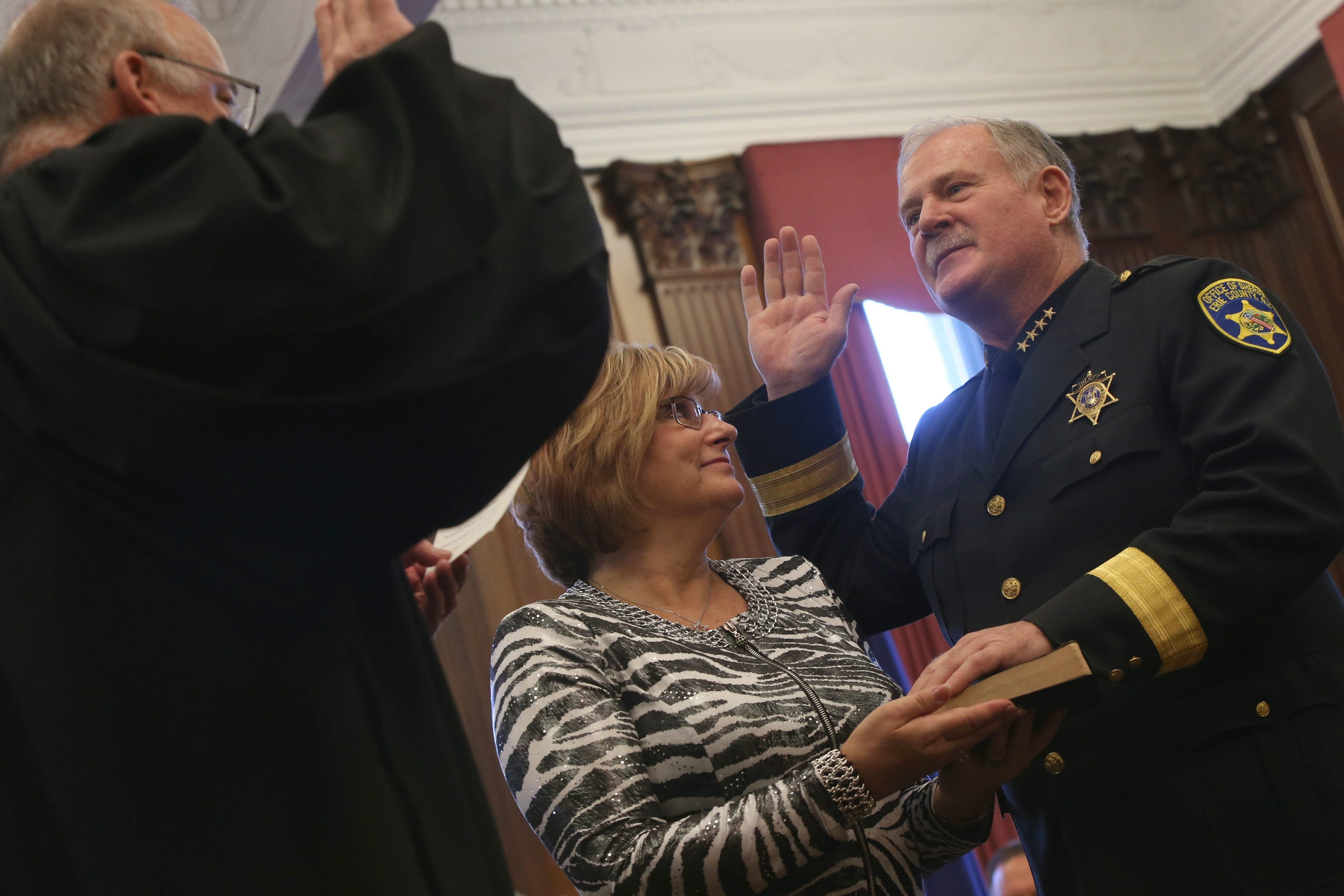 State Supreme Court Justice M. William Boller swears in Erie County Sheriff Timothy B. Howard for his third term on Monday as Howard's wife, Sue, holds the Bible. Howard said he will continue to oppose the state's gun control law.