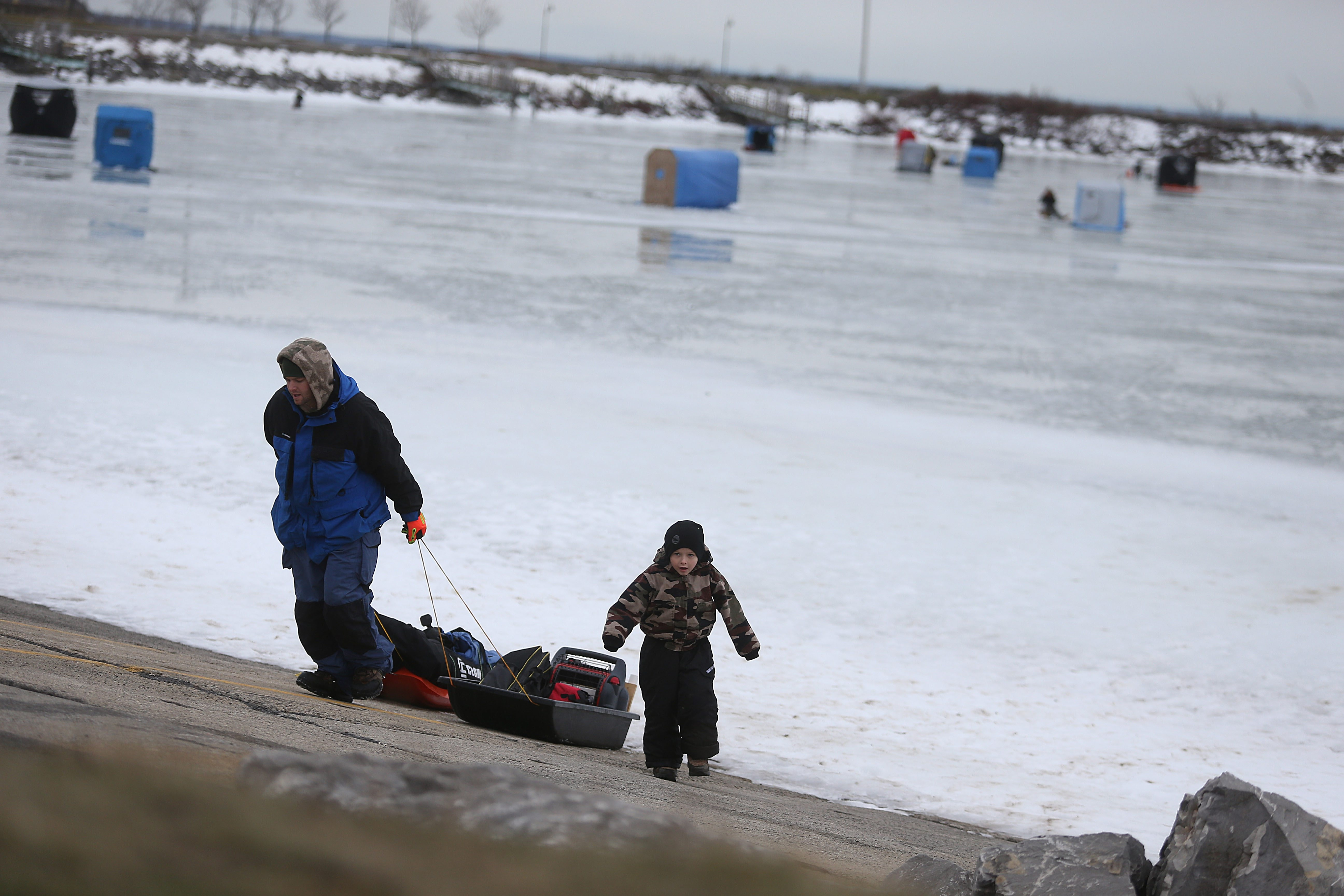 Frigid temperatures for the next few days will make ice fishermen happy. Rick Becker Sr. and his son, Rick Jr., 5, pull a sled with their ice fishing equipment off the ice near the Small Boat Harbor in Buffalo Sunday.