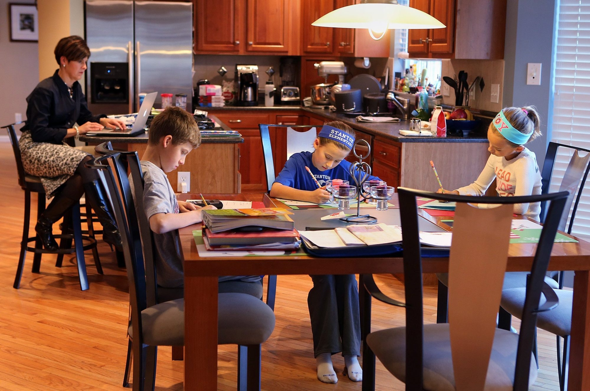 Niki Stilwell works from home in Fenton, Mo., while children, from left, Kyle, 12, Danika, 11, and Natalie, 9, do their homework, which is viewed as a tool to help master subjects but is no longer subject to being graded.