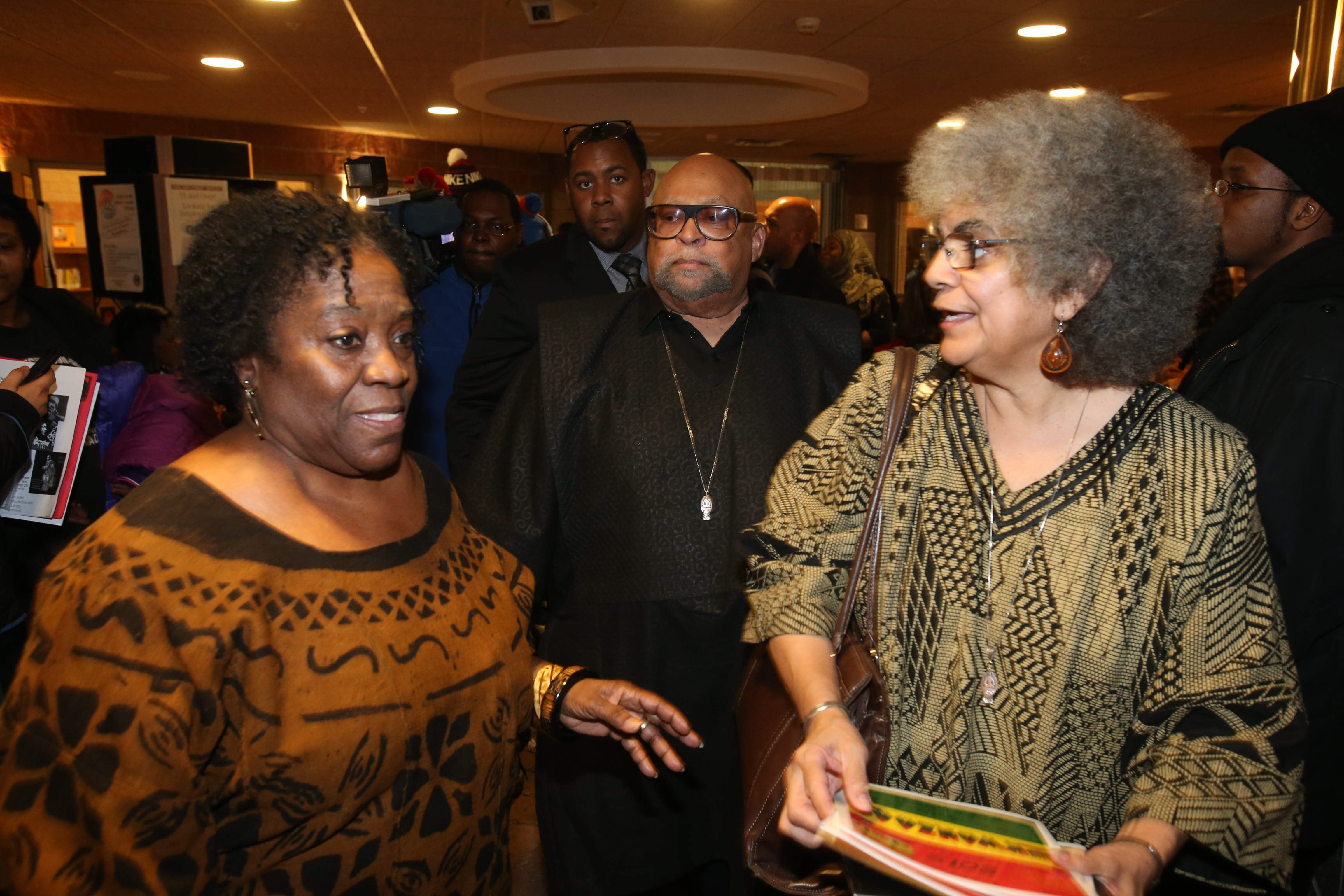 Taliba Asante, left, co-chairman of the Buffalo Kwanzaa Committee, Kwanzaa founder Maulana Karenga, center, and his wife, Tiamoyo, take part in Kwanzaa observances Sunday at the Frank E. Merriweather Jr. Library.