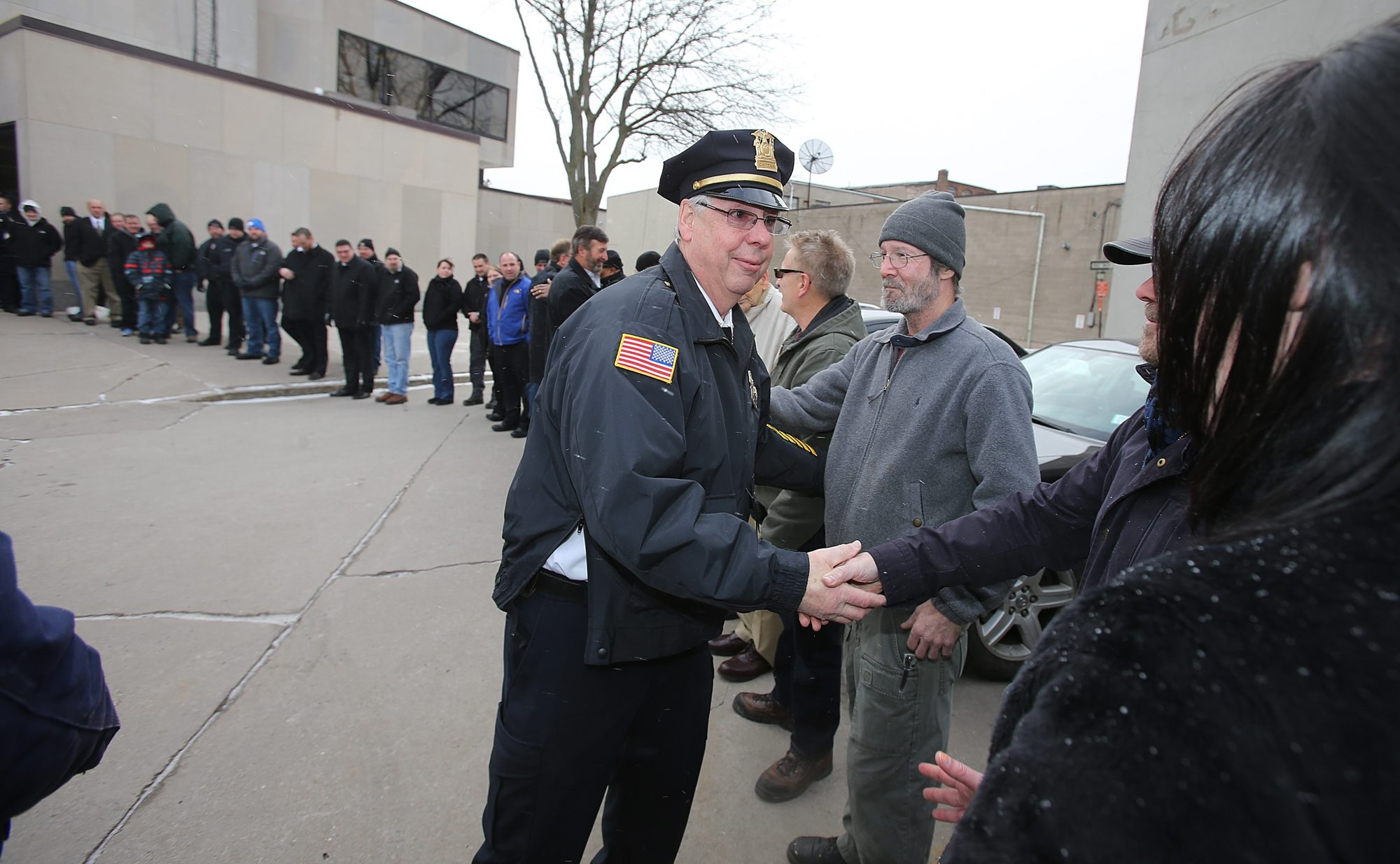 Lockport Detective Capt. Richard L. Podgers greets well-wishers Monday as he and three other retiring city police officers are given a send-off by the department and friends outside Lockport City Hall.