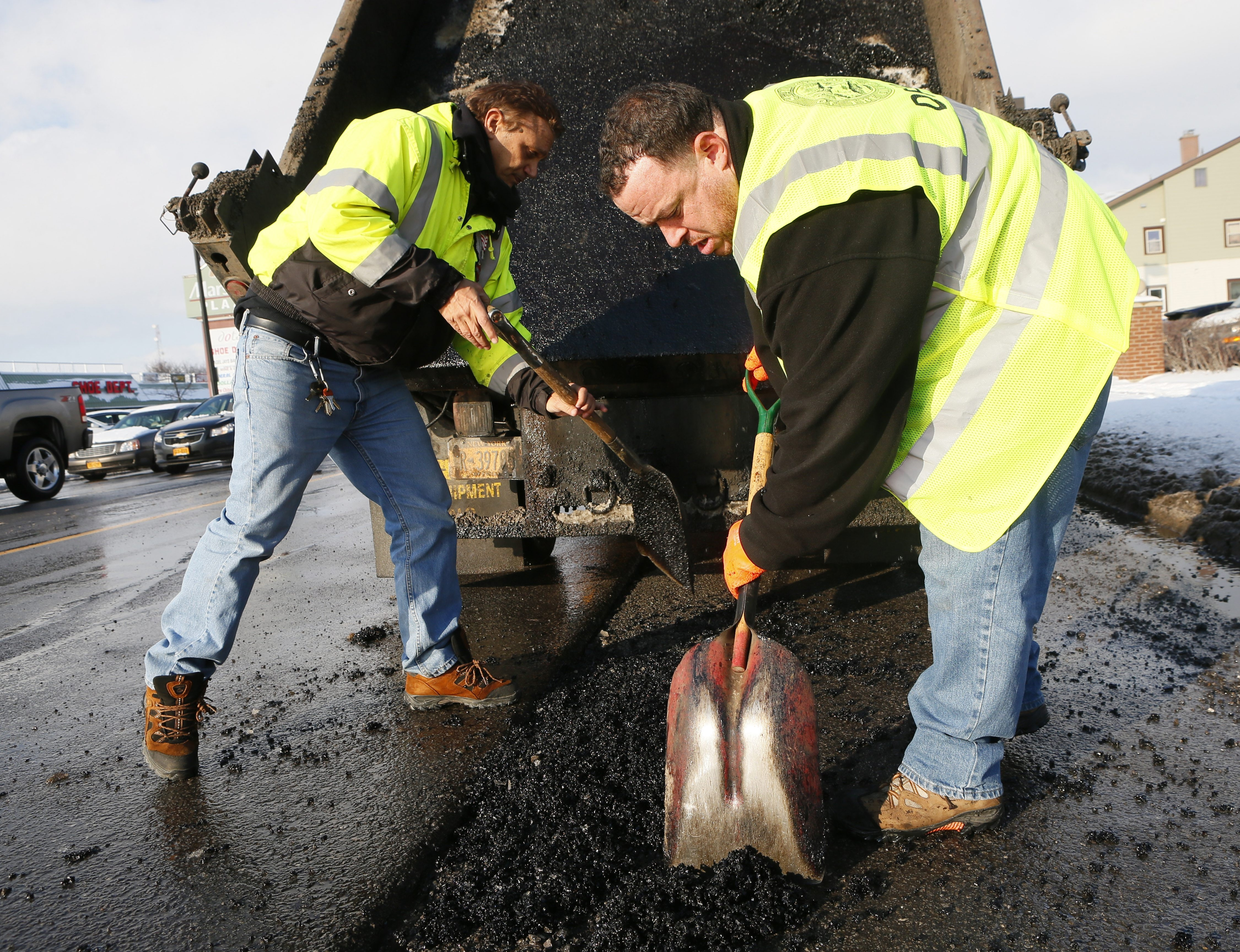 Gary Quatrani, left, and Don Allen Jr. have been on pothole duty early due to conditions that usually don't pop up until later in winter.