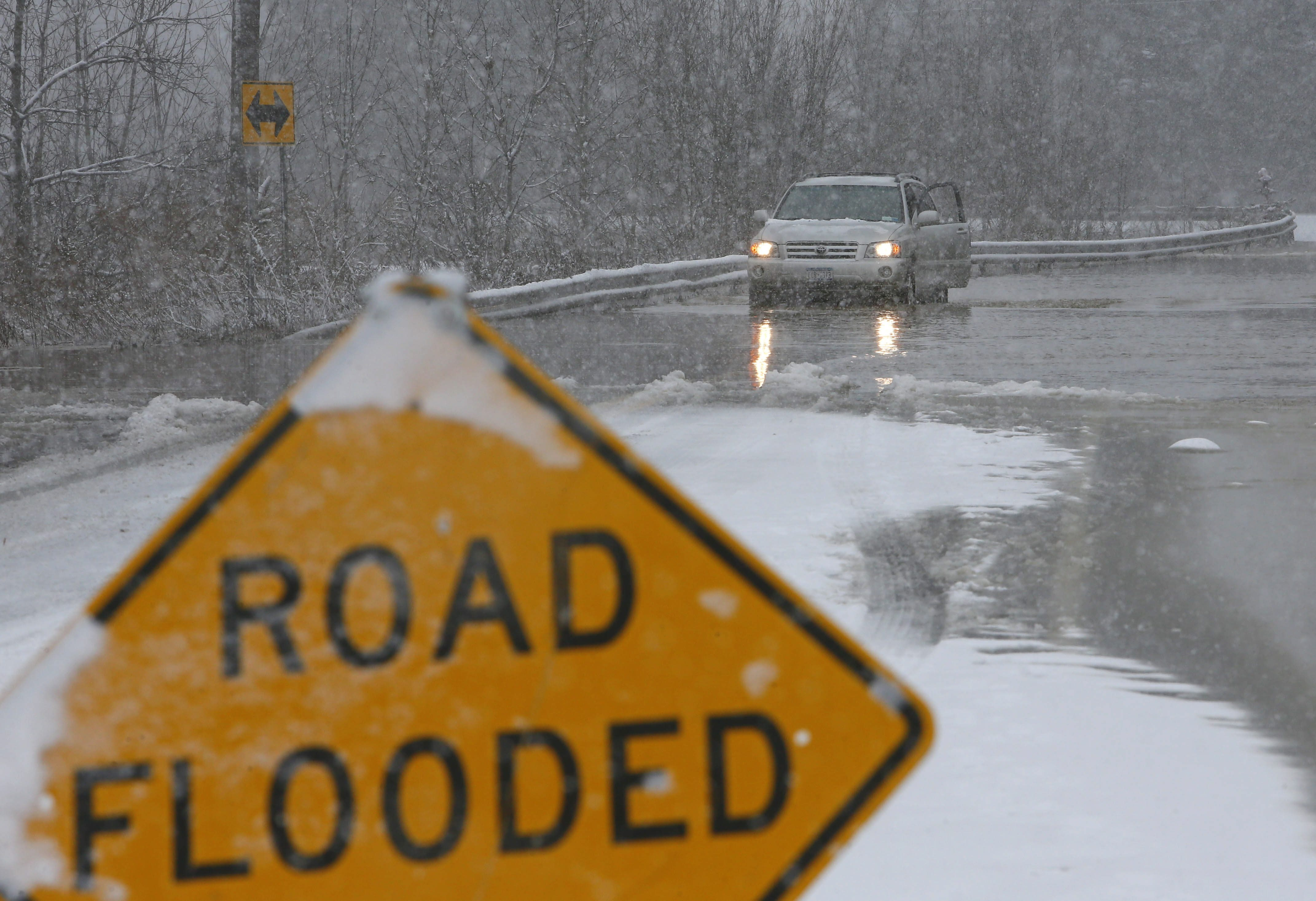 A motorist checks the height of water on Tonawanda Creek Road in Clarence on Christmas Eve.
