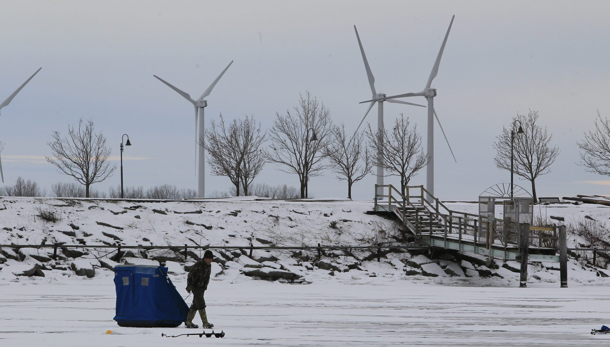An ice fisherman pulls his shelter at the Small Boat Harbor on Christmas Day.