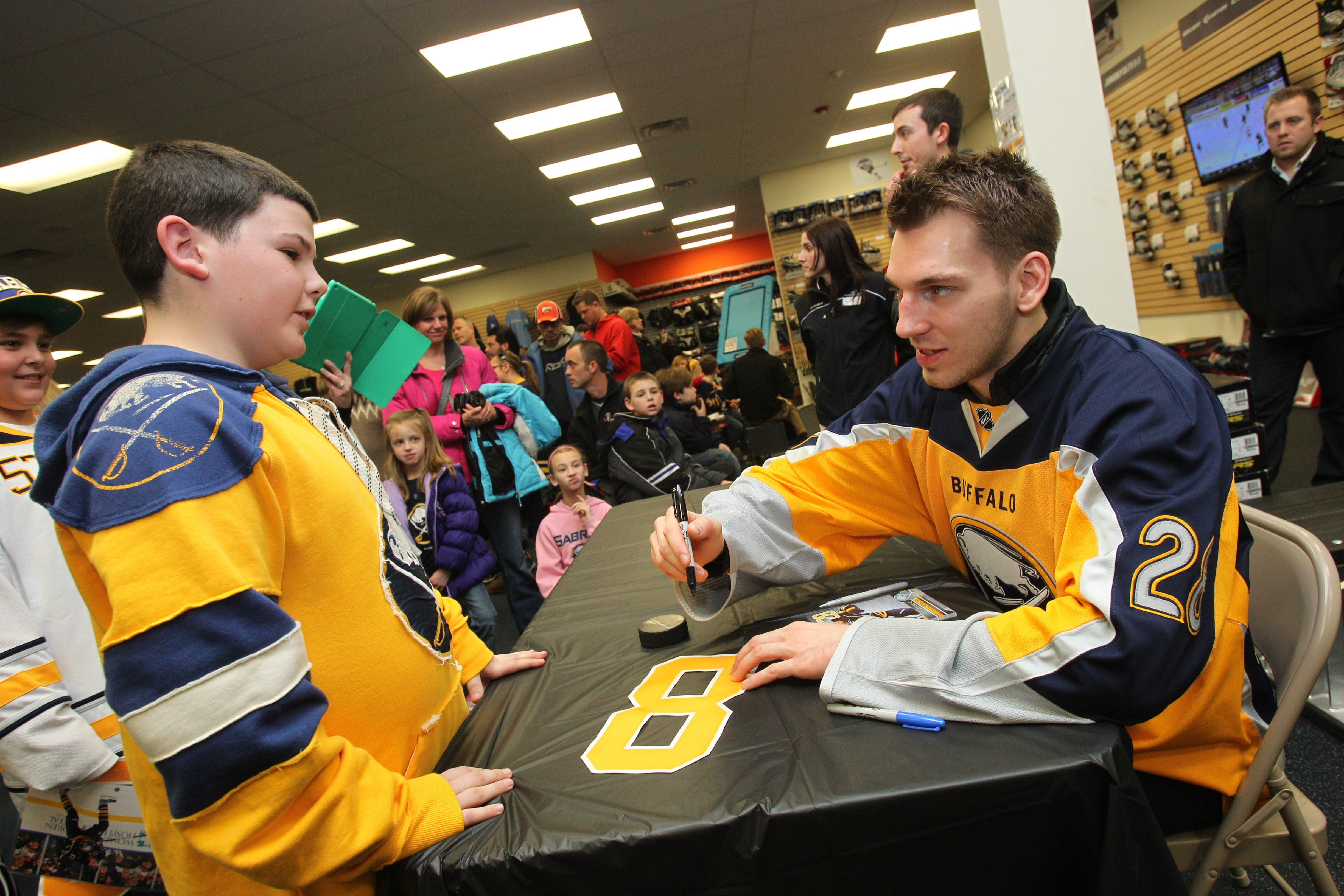 Anthony Aiello, 12, of the Town of Tonawanda, gets an autograph from Buffalo Sabre Zemgus Girgensons at Pure Hockey in Amherst, one of the collection sites for the Good Neighbor Skate Drop-Off.
