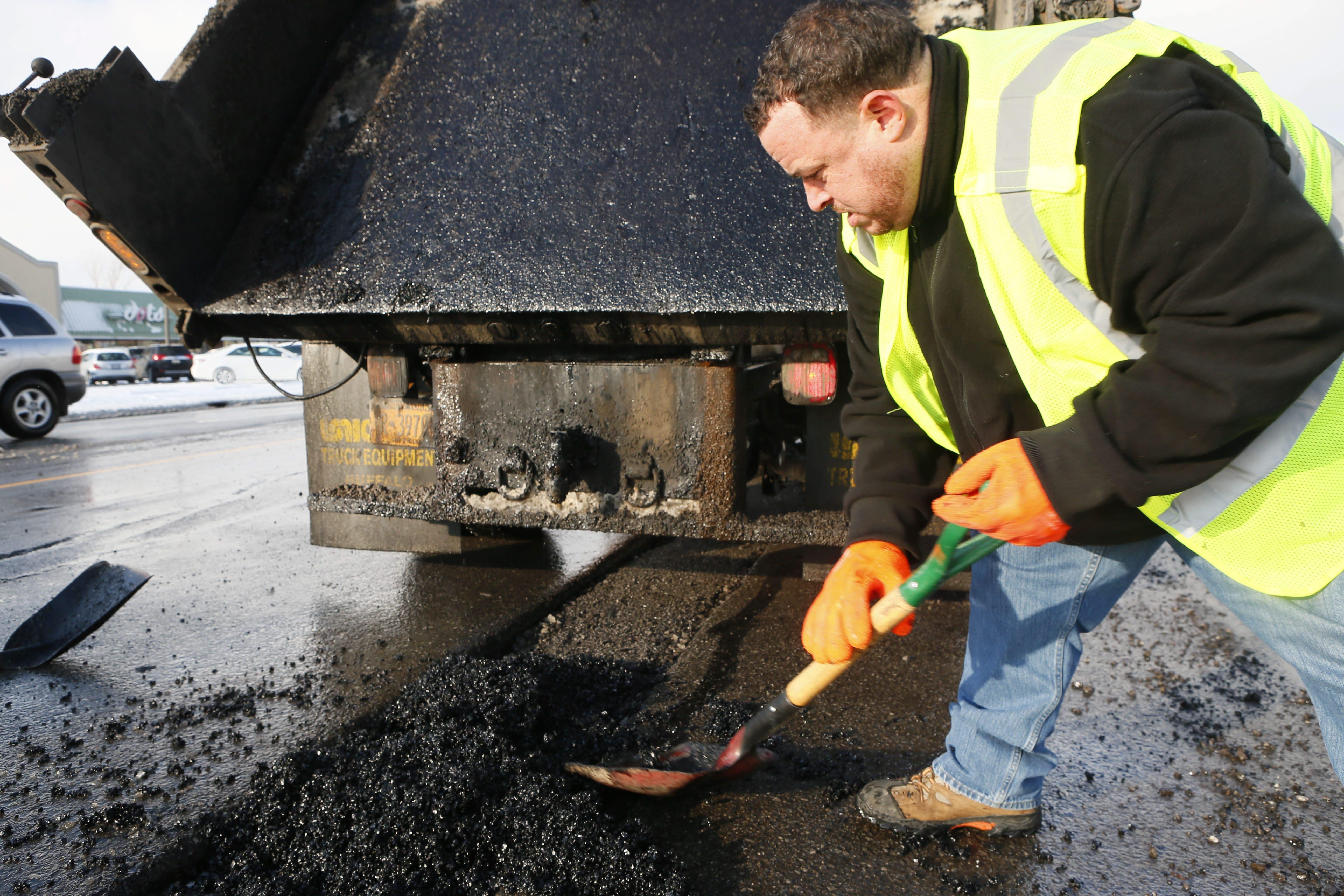 "Don Allen Jr. shovels ""cold patch"" into a large pothole on Delaware Avenue in Buffalo."