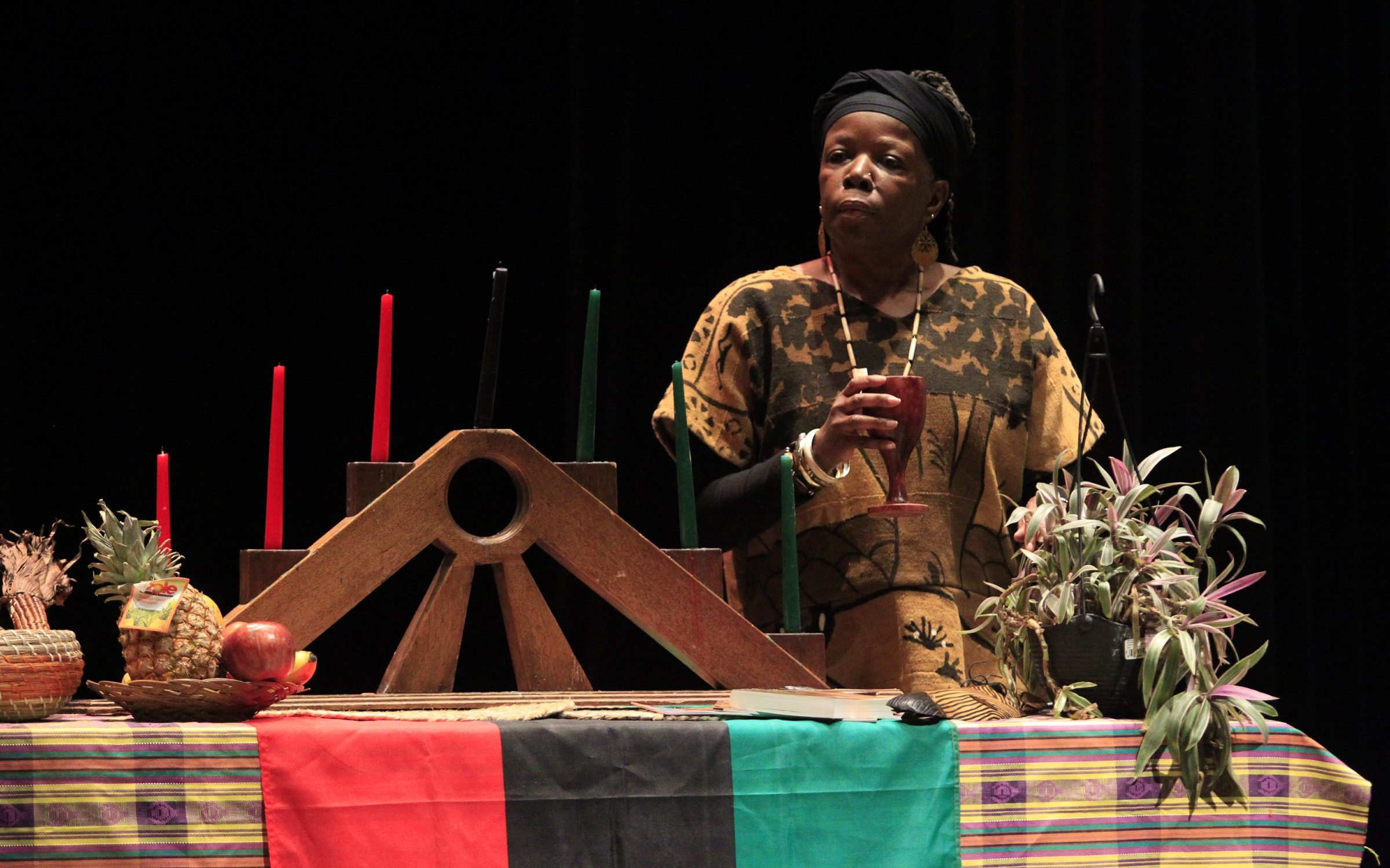 Karima Amin pours water during the libation on the opening of Kwanzaa at the Buffalo Academy for the Visual and Performing Arts.