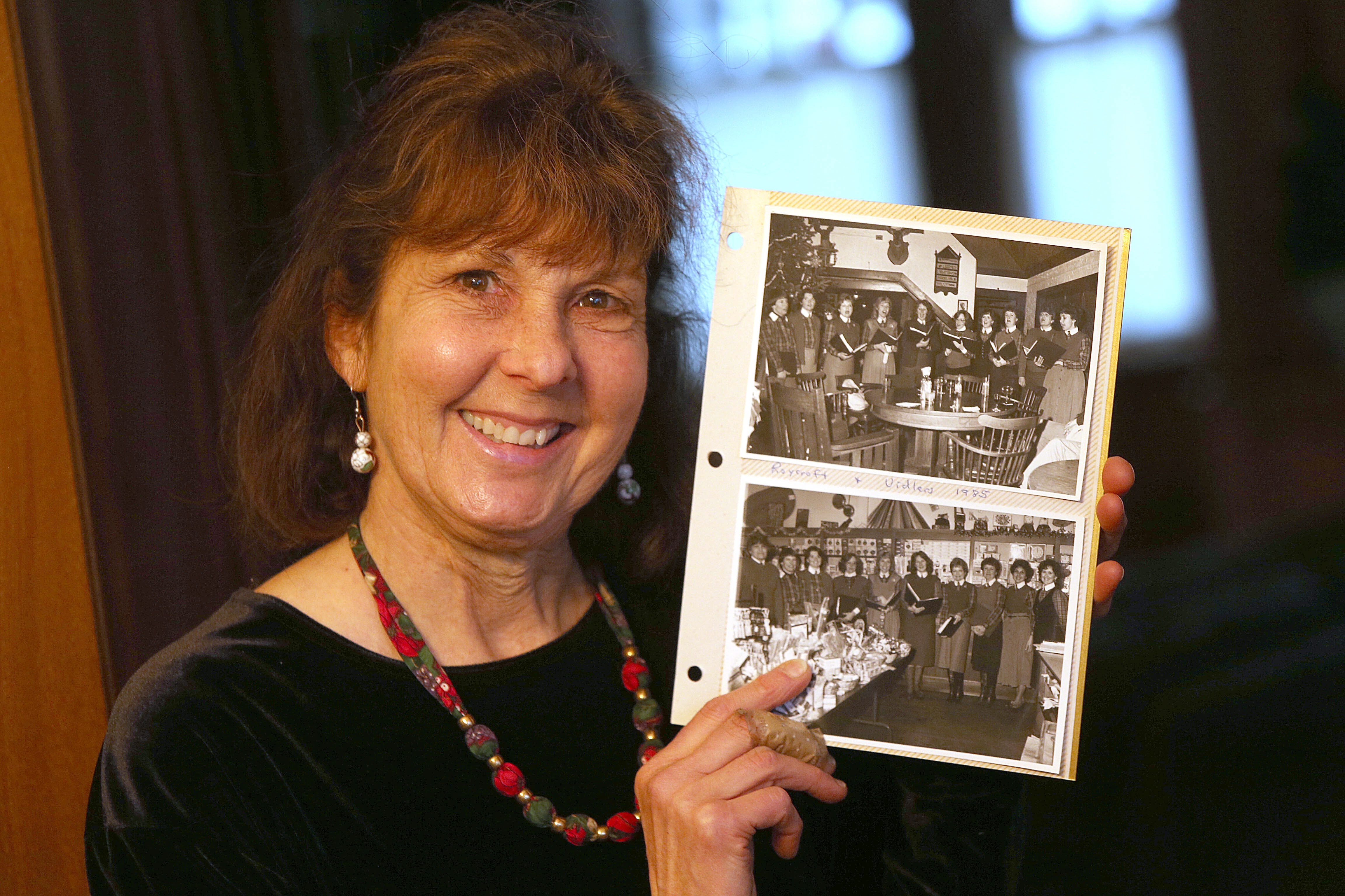 Ellen Moomaw holds up some black and white photos of the Village Singers from her collection on Thursday.