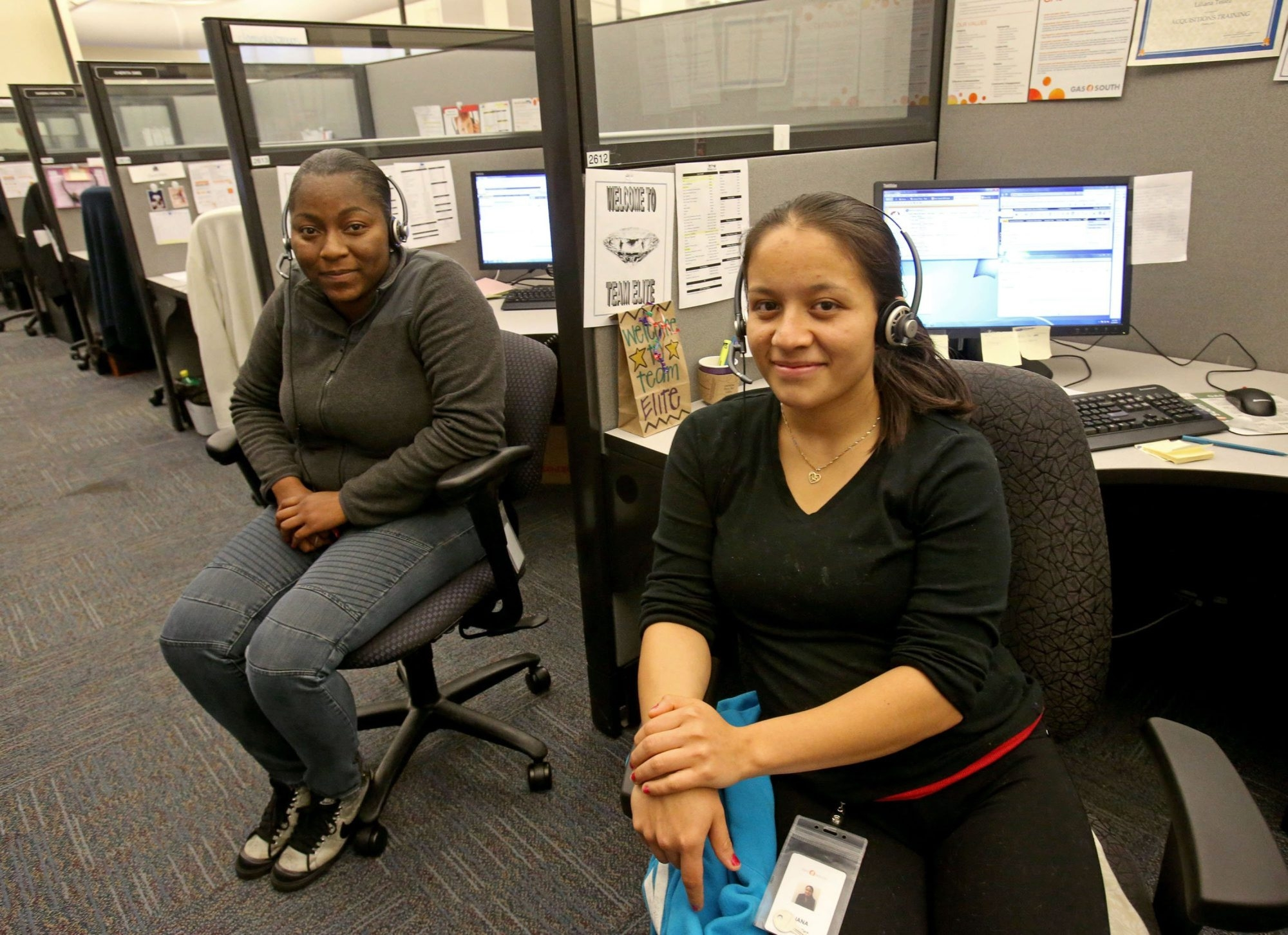 Gas South customer service representatives Jomicka Green, left, and Liliana Tapia next to their cubicles in the customer care department  in Marietta, Ga.
