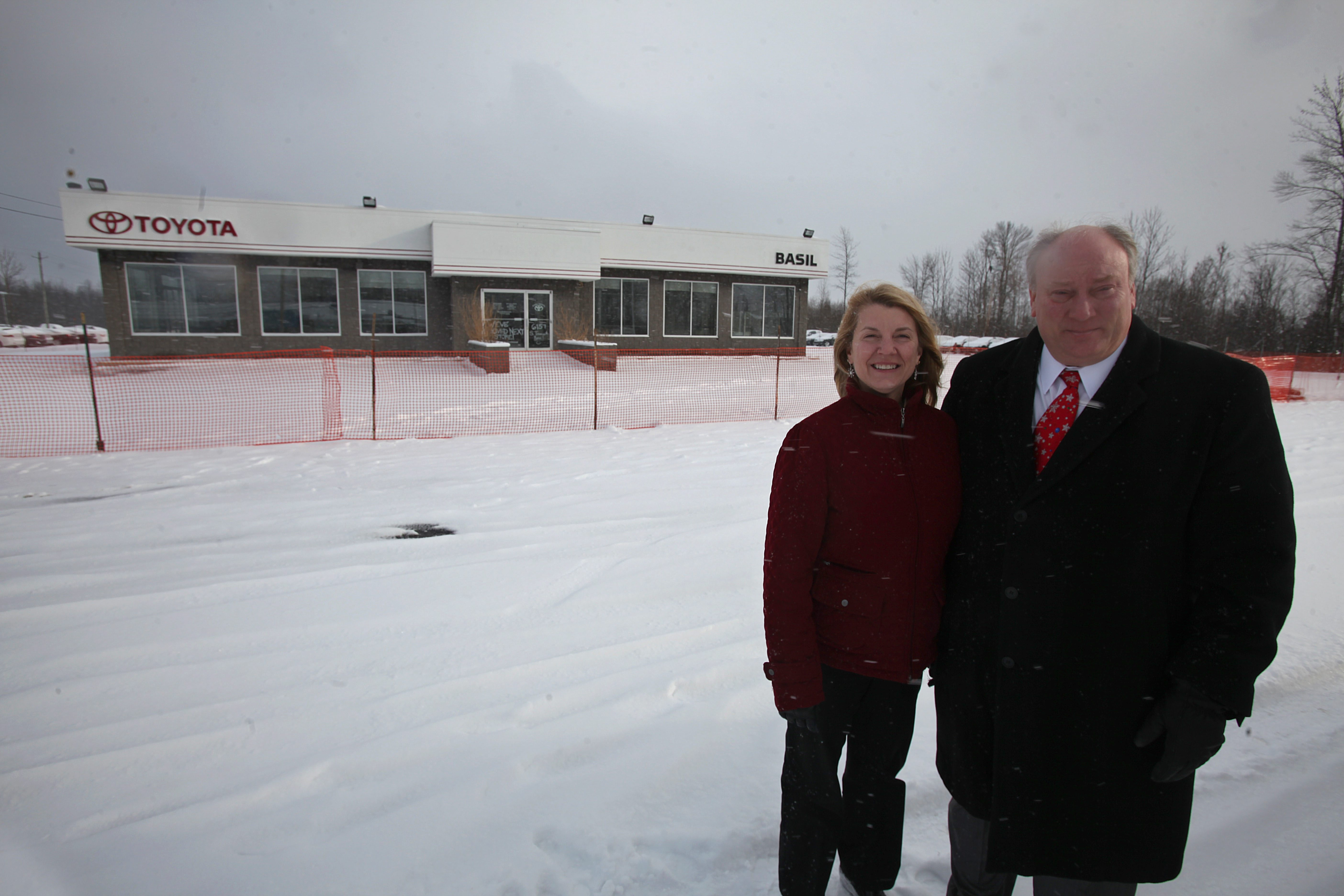 Michael Basil stands with his wife, Faith, outside the site where work is set to begin Thursday on the new Basil Volkswagen dealership at 6179 S. Transit Road in Lockport.
