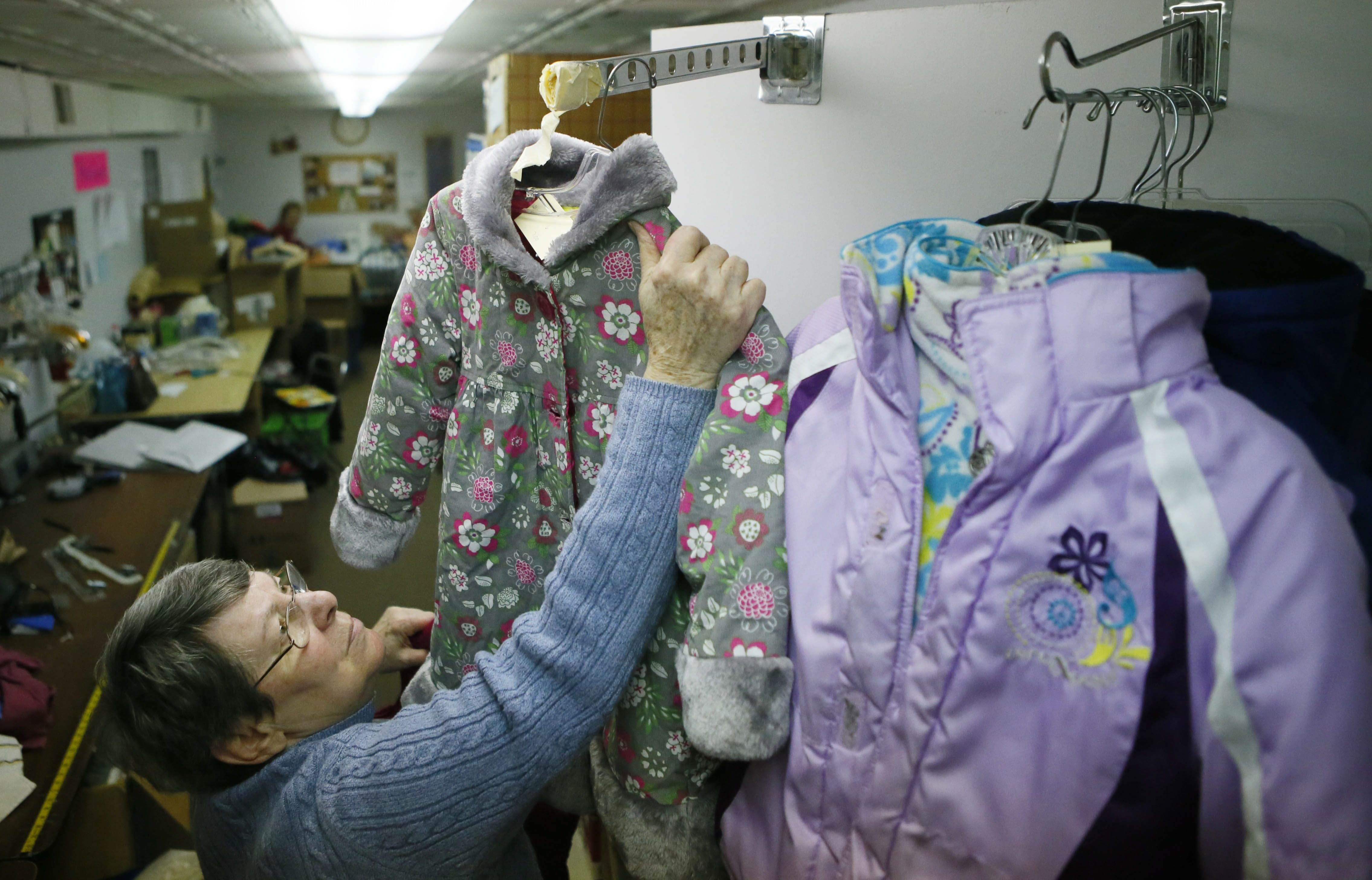 Norma Hartzell sorts coats donated by Canisius students at Ladies of Charity.