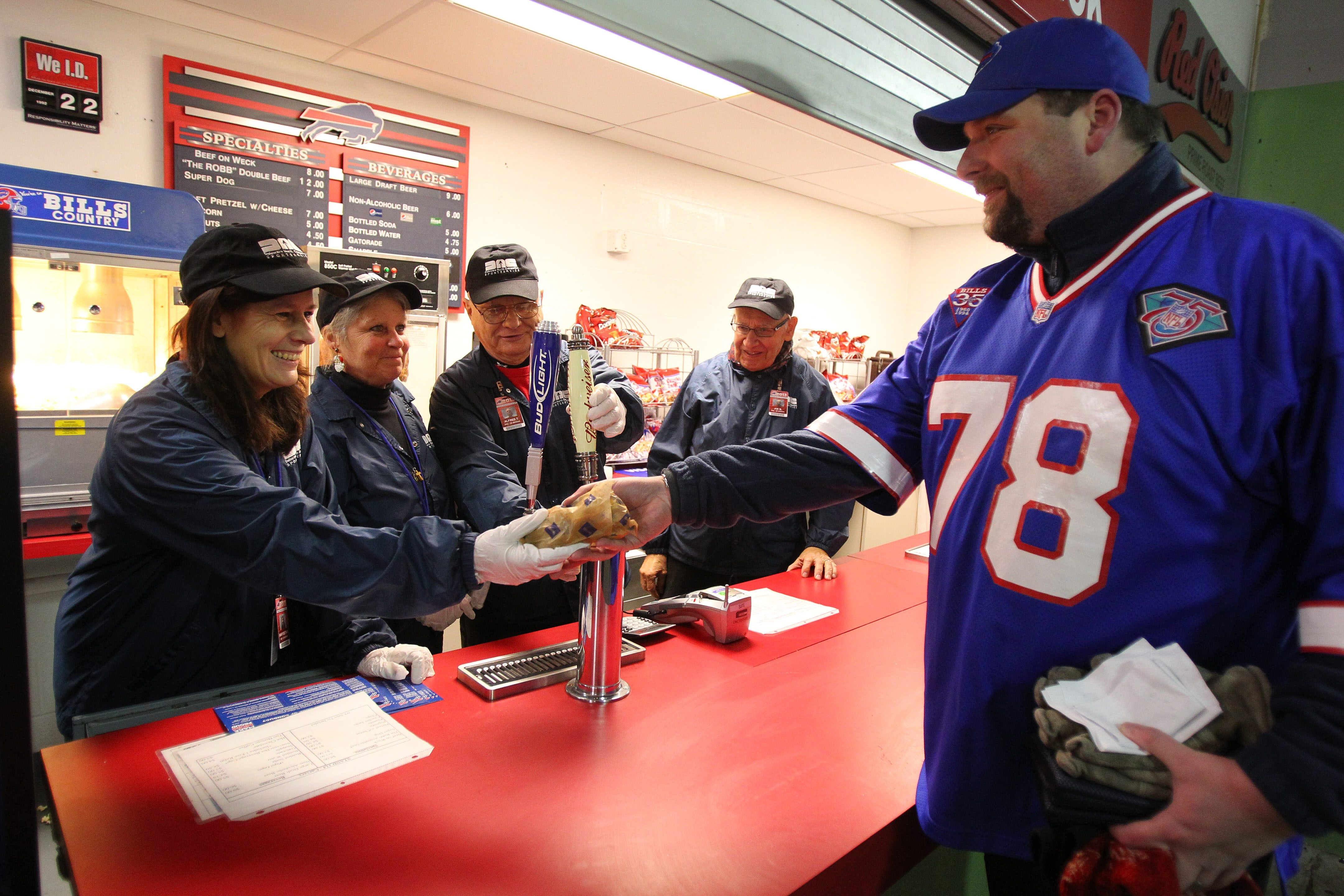 Ryan Harrison, right, is helped by, from left to right, Mary Beth Van Lew, Barb Rotino, Al Szymanski and Joe Manuel at stand 114 in Ralph Wilson Stadium in Orchard Park on Sunday.