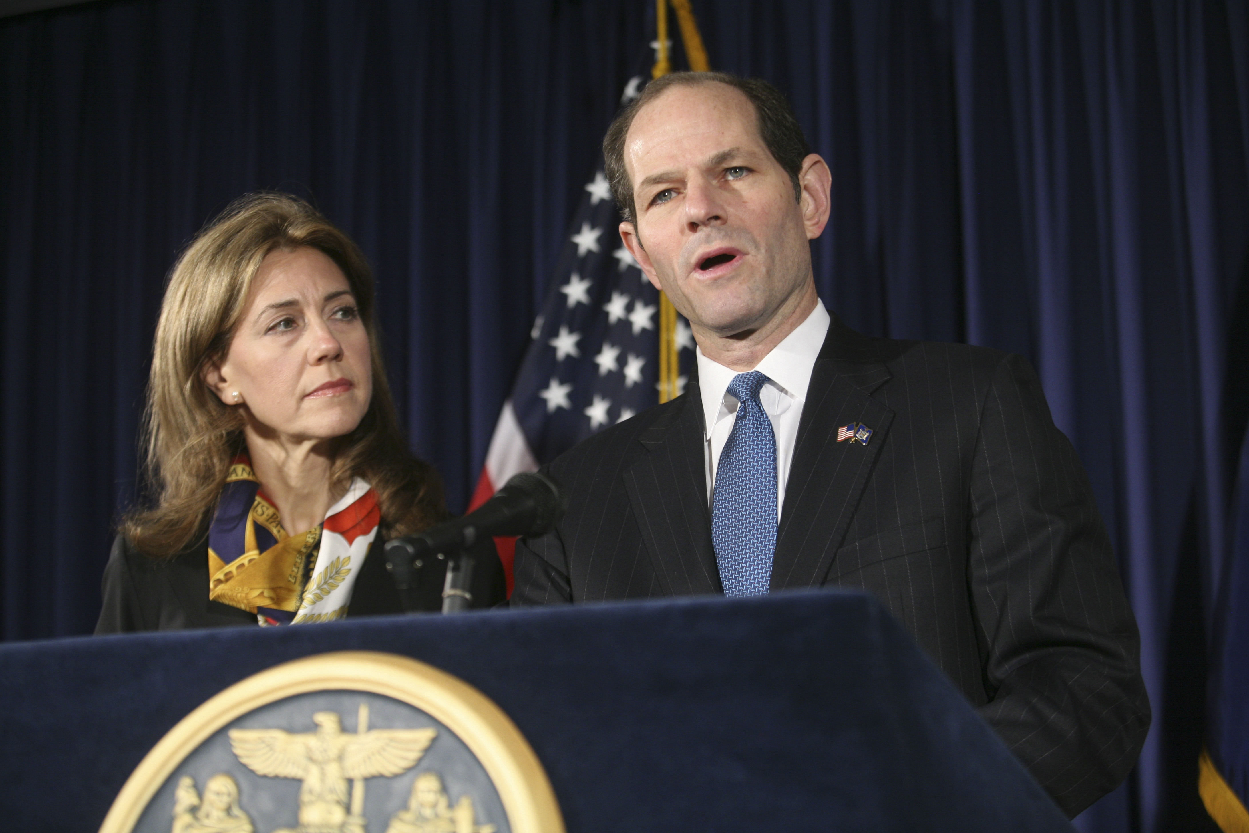 """FILE — Silda Wall Spitzer stands by her husband, Eliot Spitzer, as he announces his resignation as governor, in New York, March 12, 2008. Two decades worth of political sex scandals gave playwright Bruce Norris inspiration for his new dark comedy """"Domesticated"""", an examination of the compromises inherent in all marriages. (Hiroko Masuike/The New York Times) PHOTO MOVED IN ADVANCE AND NOT FOR USE – ONLINE OR IN PRINT – BEFORE OCT. 27, 2013."""
