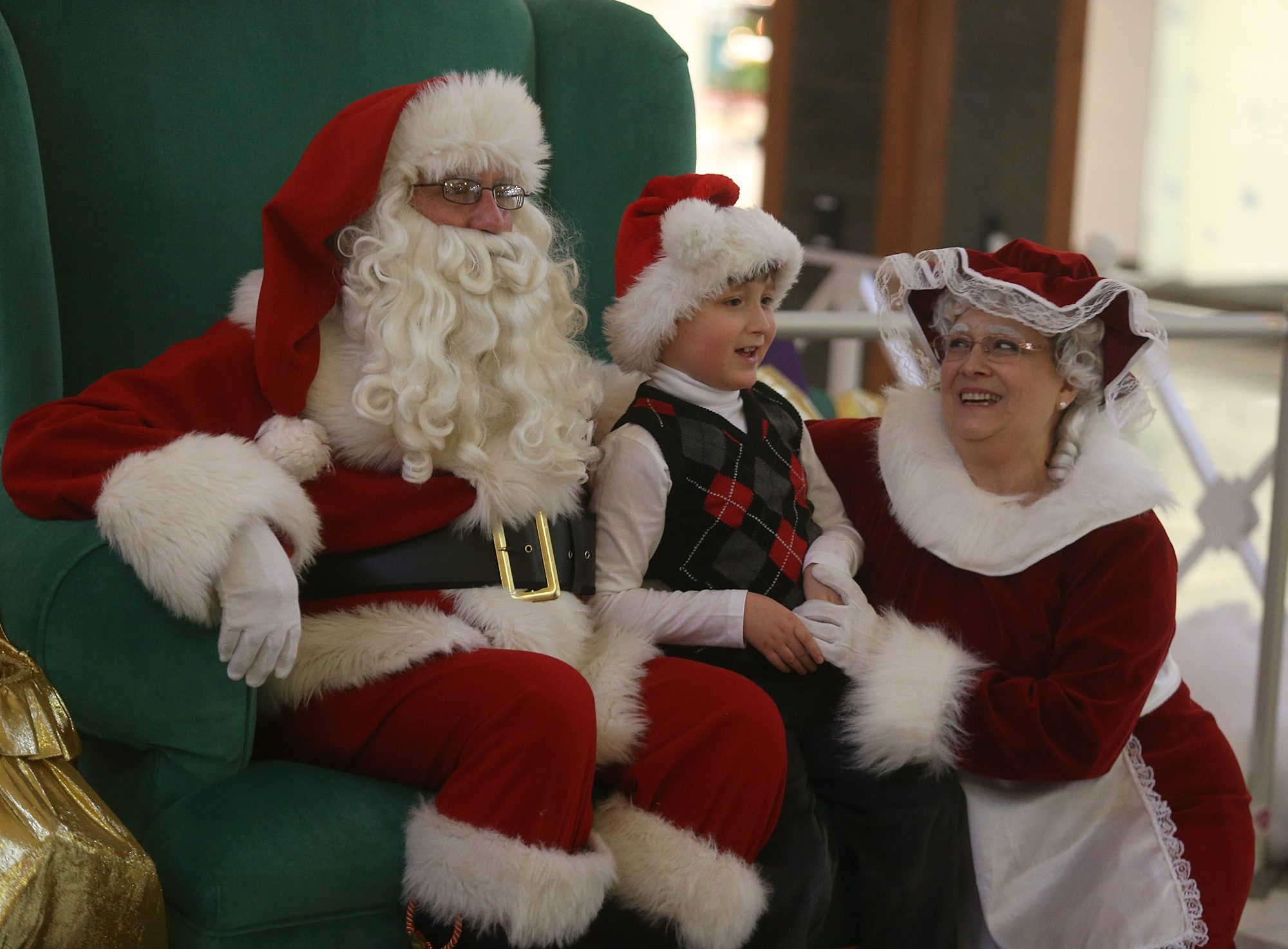 """Joshua Mattioli, 7, of Hamburg, enjoys a visit with Santa and Mrs. Claus at the Eastern Hills Mall during a special """"Patient Santa"""" program for autistic children Sunday."""
