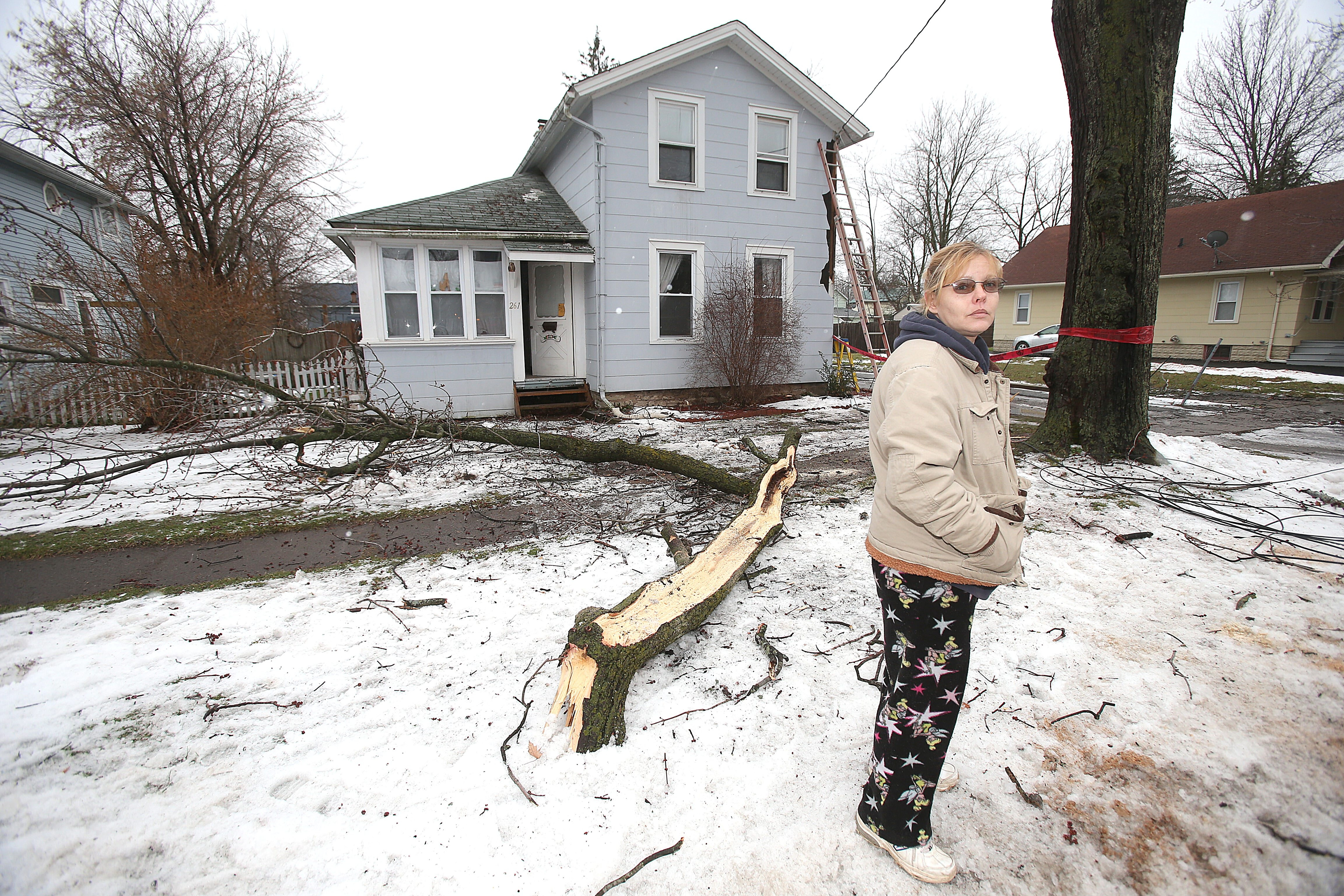 Liz Curtis, of Grand Street in Lockport, waits for crews to restore power after tree limbs ripped lines from her home. The lights came on at about 2:30 Monday afternoon after about 24 hours.