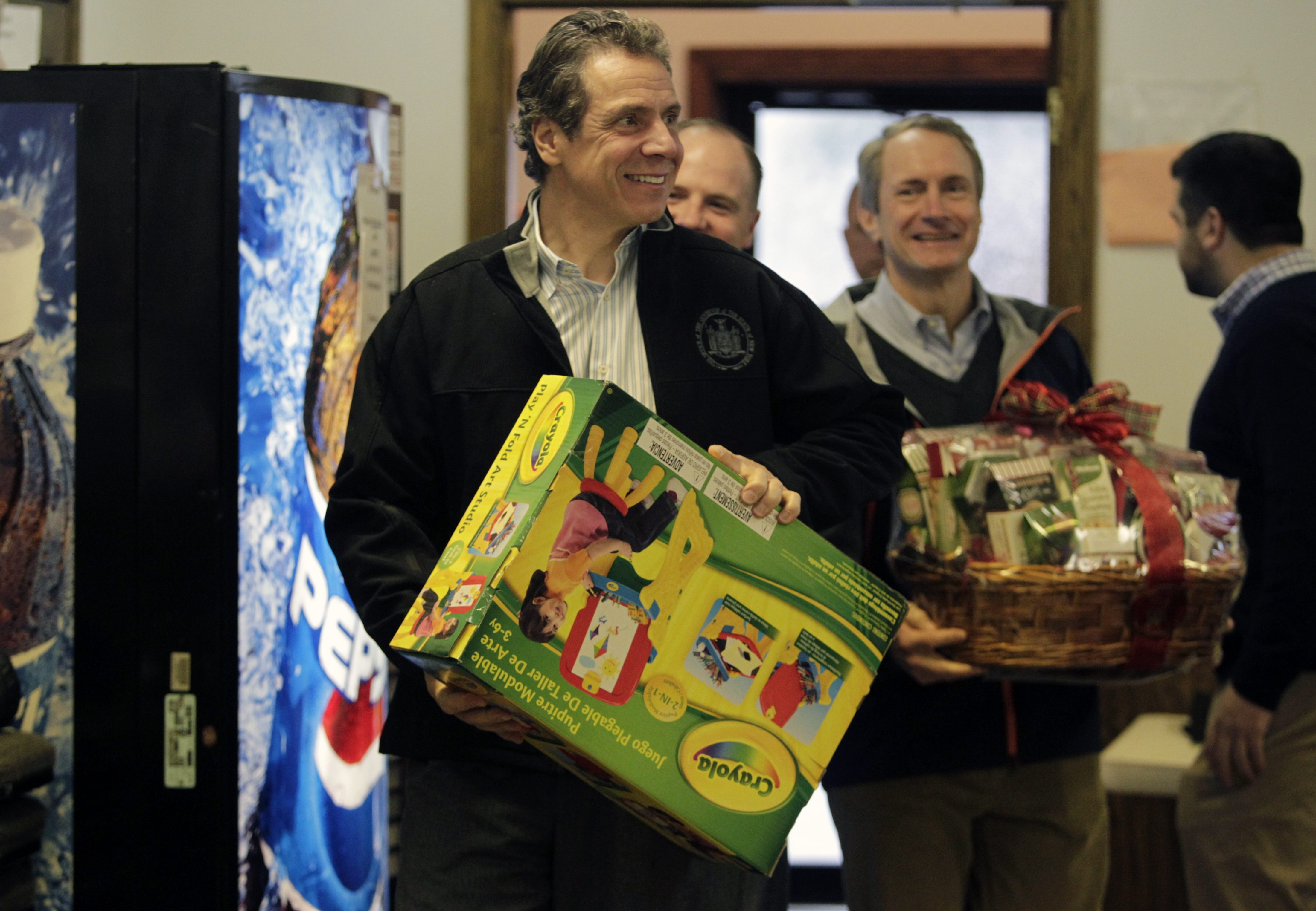Gov. Andrew M. Cuomo carries Christmas presents into the Second Baptist Church in Lackawanna on Saturday.