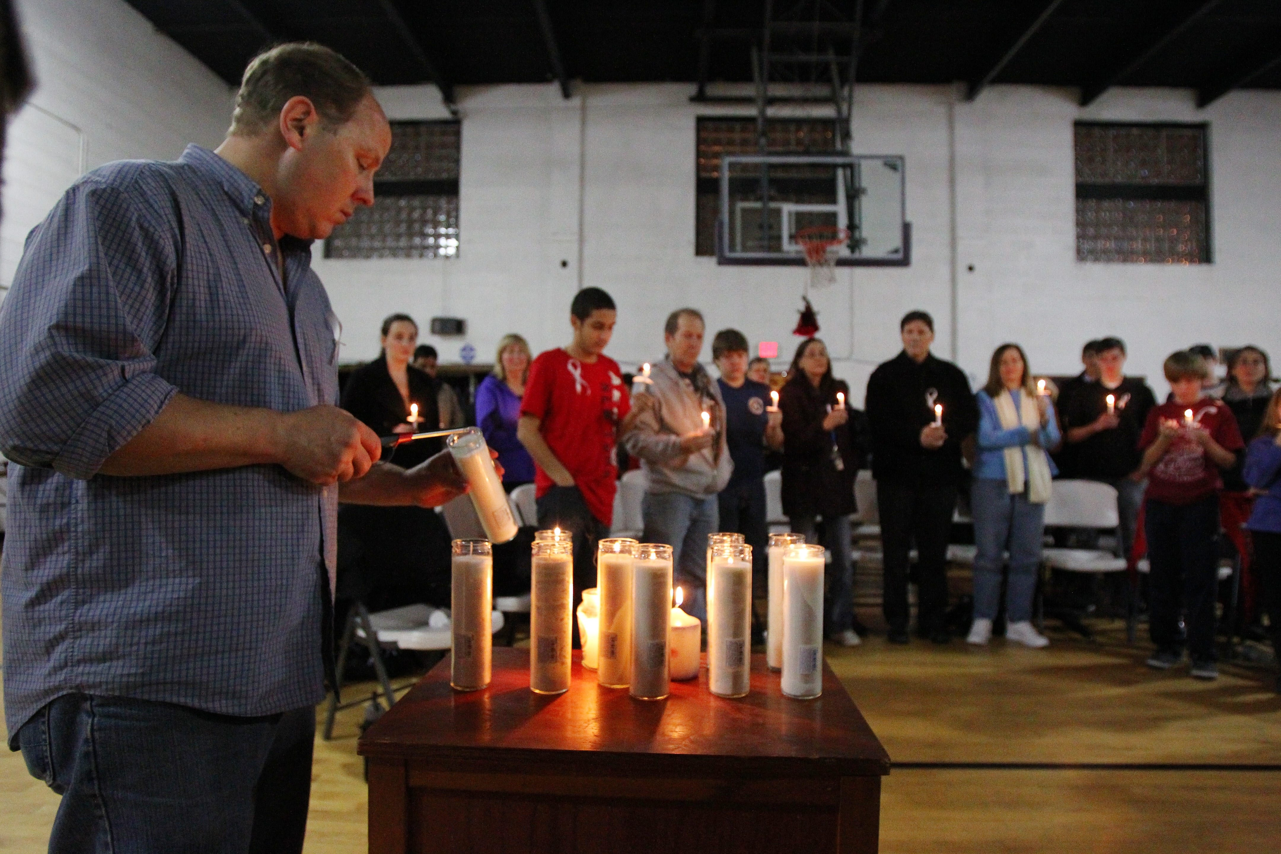 Volunteer Peter Warn lights candles for each of the nine homeless people who died in the Buffalo area this year during a memorial service Saturday at the Lt. Col. Matt Urban Hope Center.
