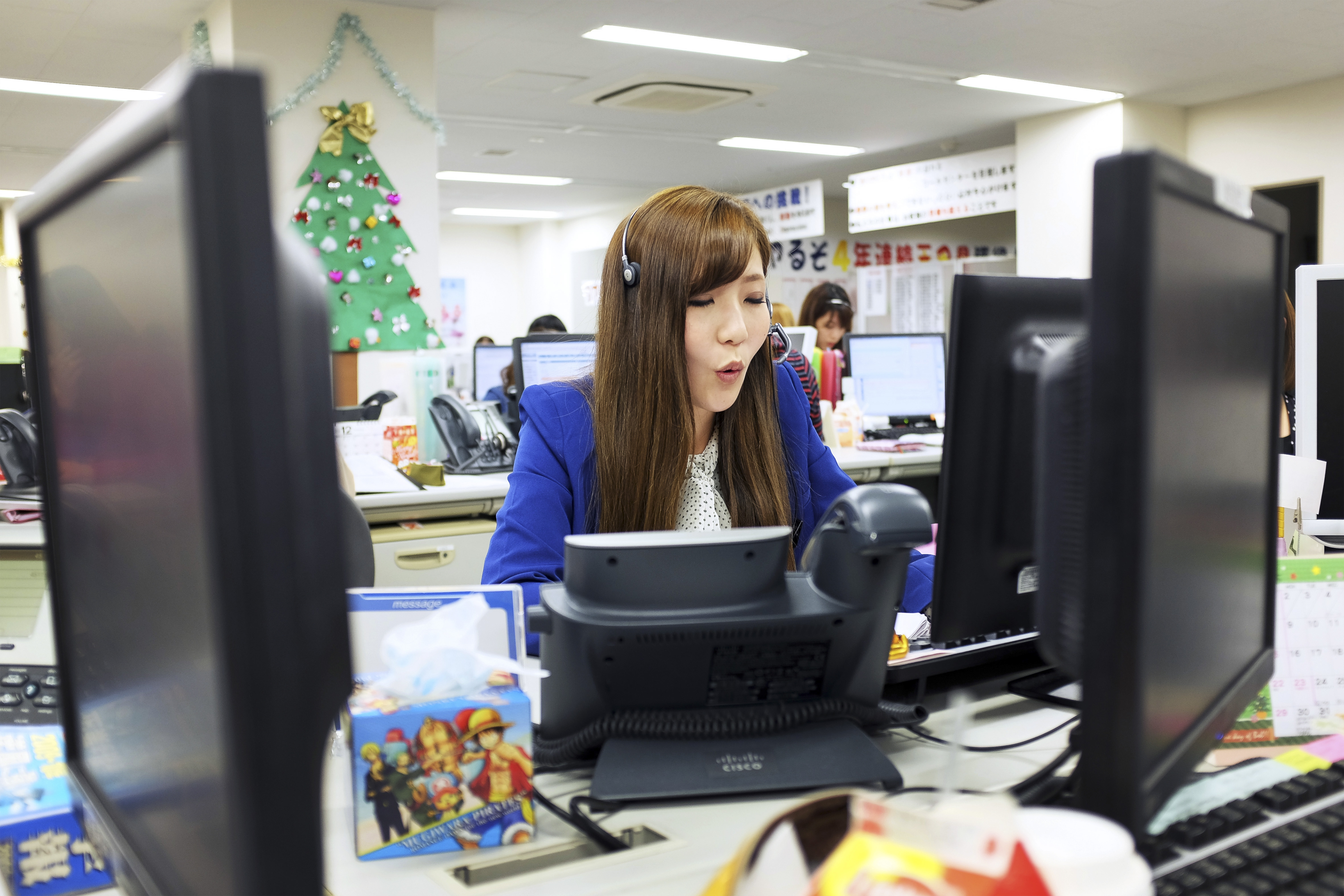 Mika Otani, a top-20 finisher in the 52nd All-Japan Phone-Answering Competition, speaks to a caller at her desk in Tokyo last week. Even as attitudes toward gender roles and office life evolve in Japan, telephone etiquette remains a deadly-serious matter, and firms sent a record 12,613 entrants this year to the competition.