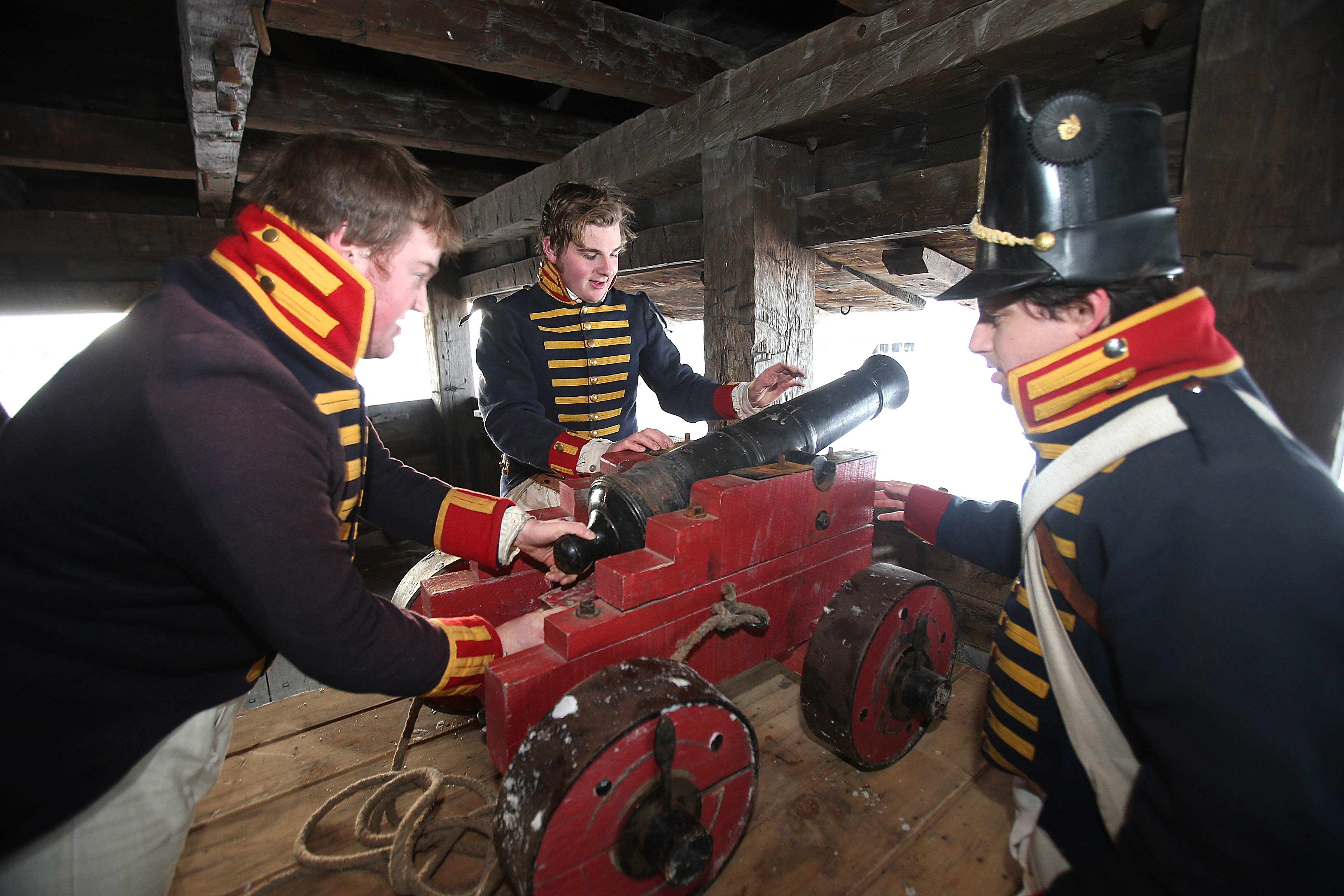 Ryan Clark, left, Robert Gerst, center, and Brian McDonald position a cannon at Old Fort Niagara Wednesday.