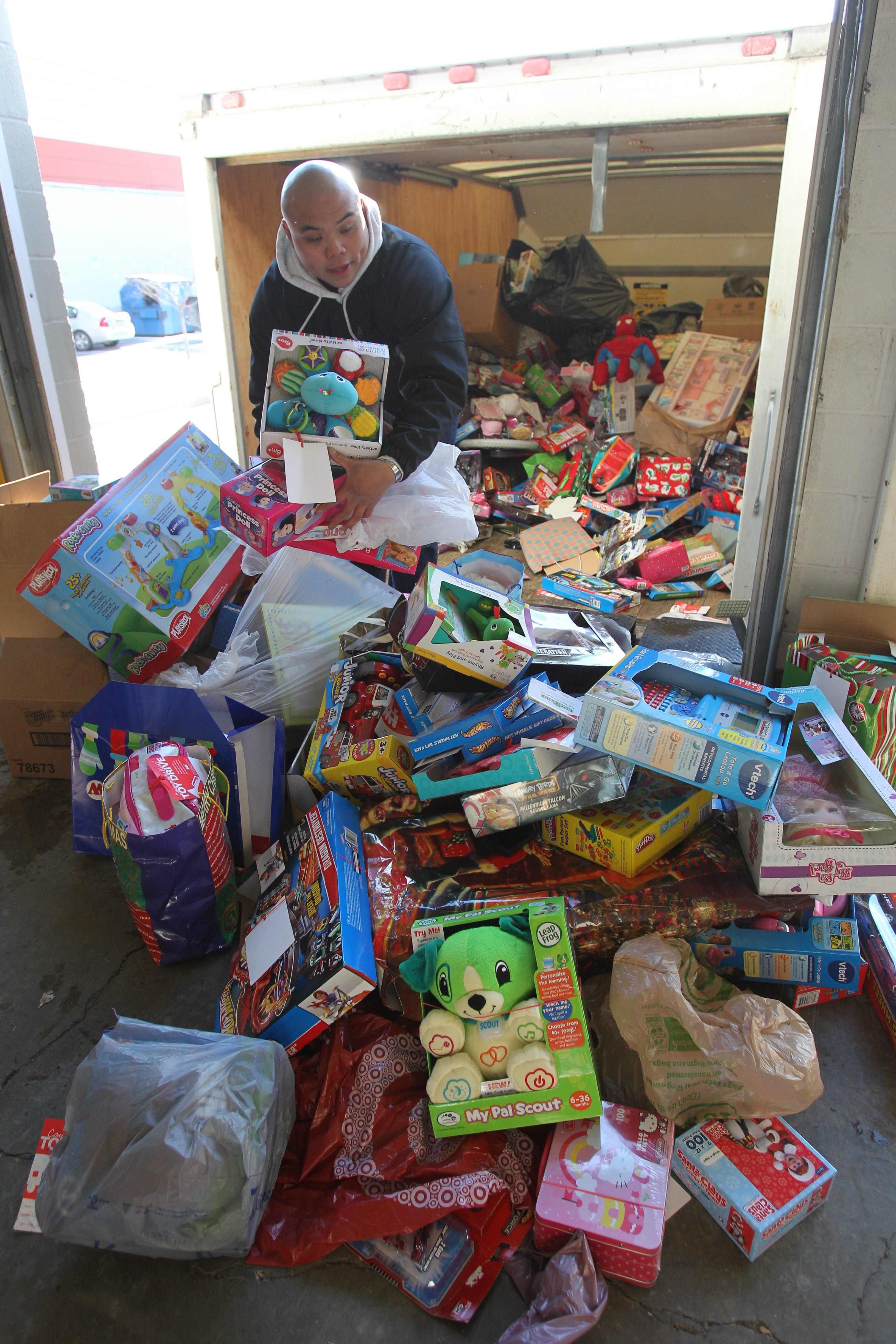Justin Ramos helps unload toys picked up from collection sites by Marine Corps reservists at the suburban warehouse donated for use by The News Neediest.