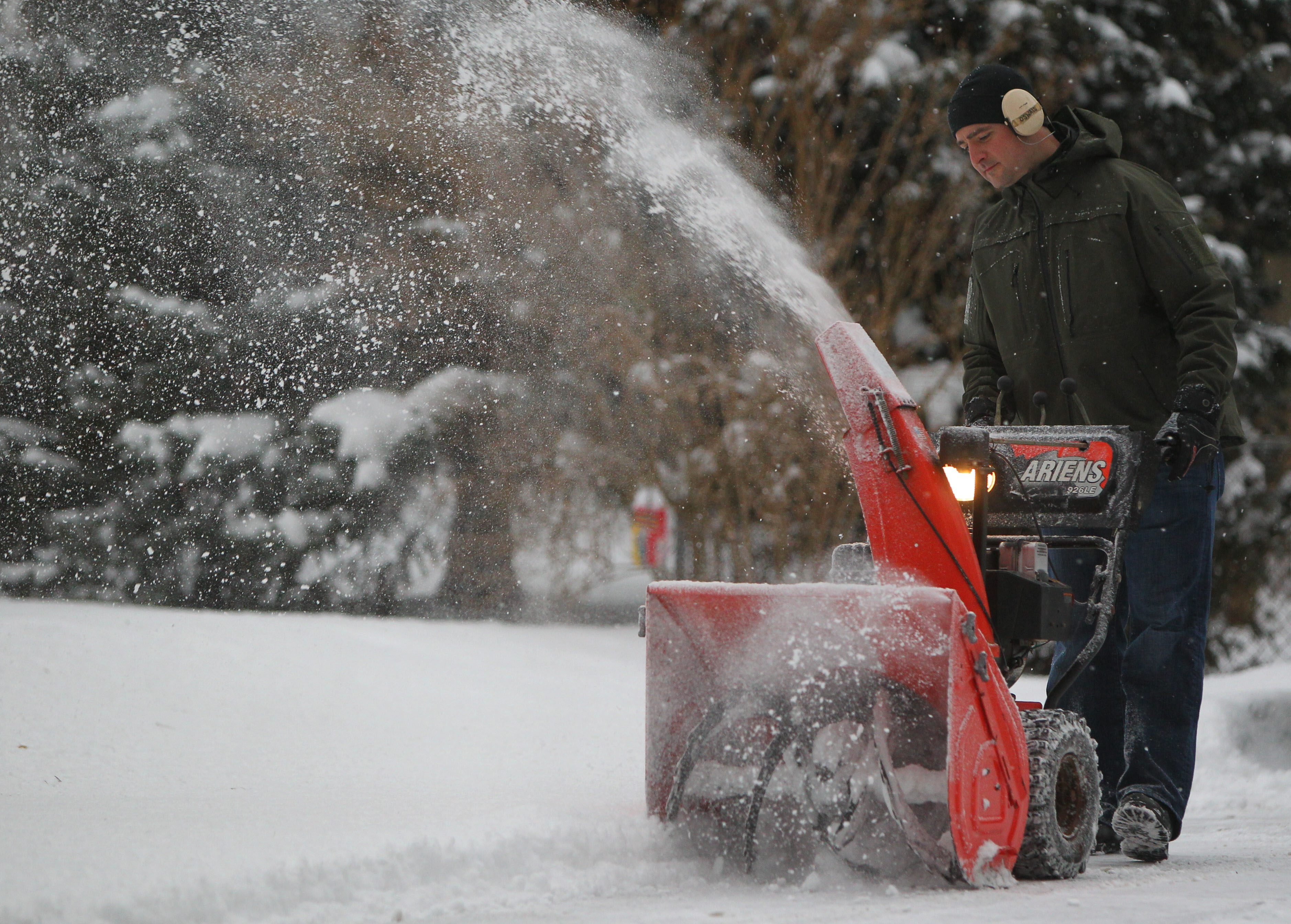 Bo Oswald uses a snowblower to clear the driveway of his Orchard Park home Friday. (Mark Mulville/Buffalo News)