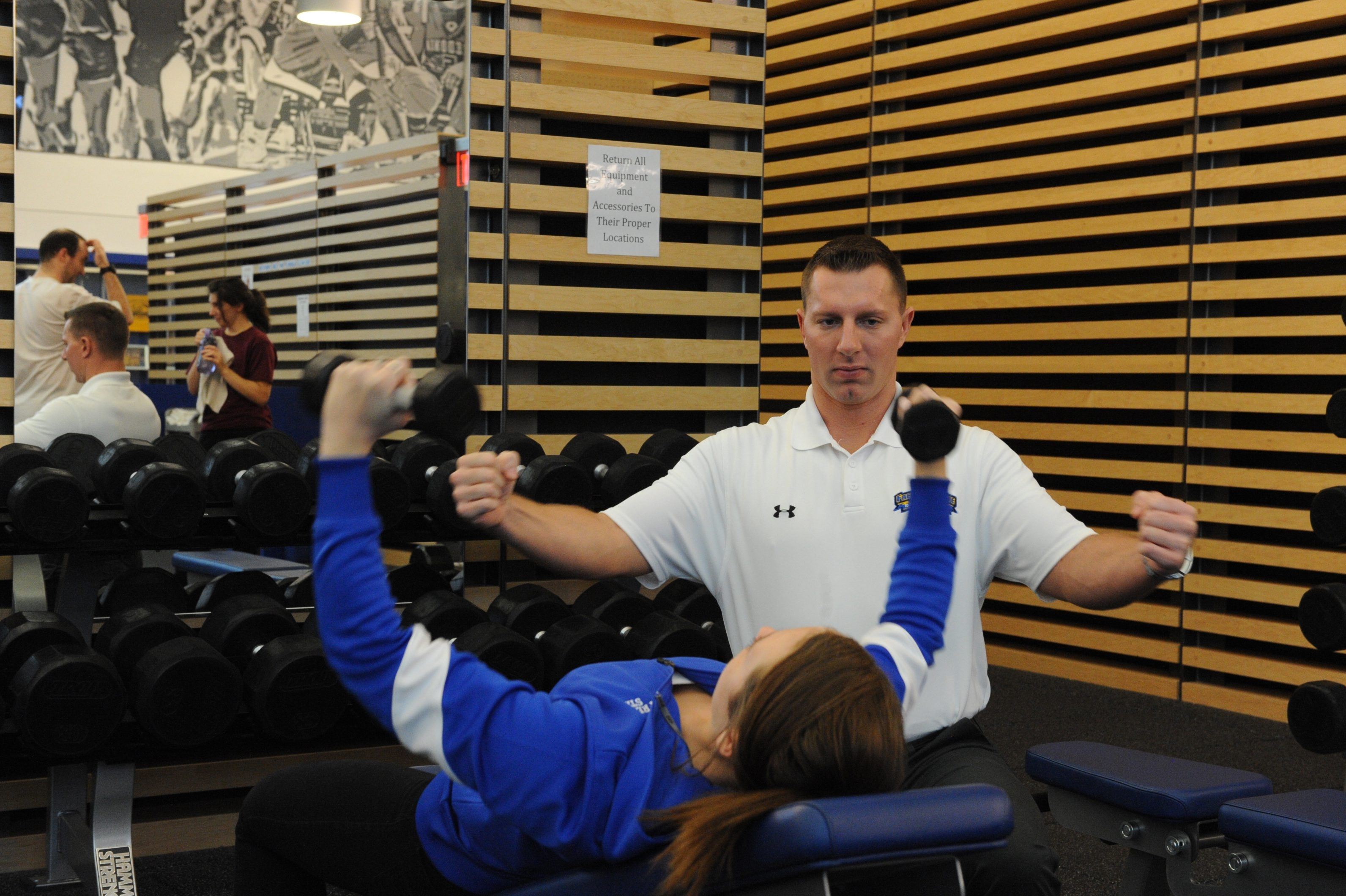 Jason Bishoff, director of the fitness center at Fredonia State College, works with Olivia Phillips, who is majoring in exercise science.