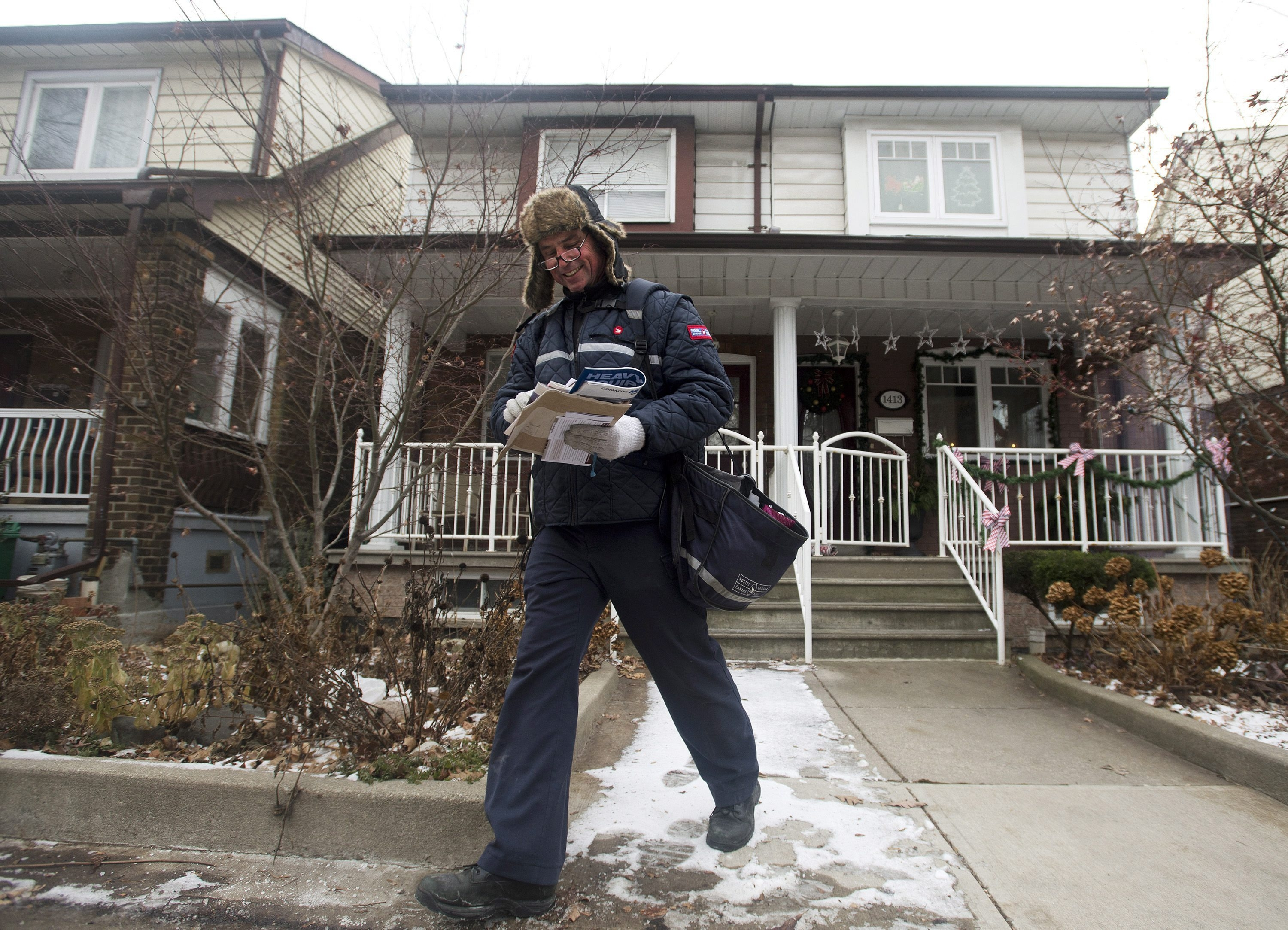 A Canada Post employee delivers mail and parcels to residential homes in Toronto on Wednesday. Canada's postal service plans som drastic changes to its service.