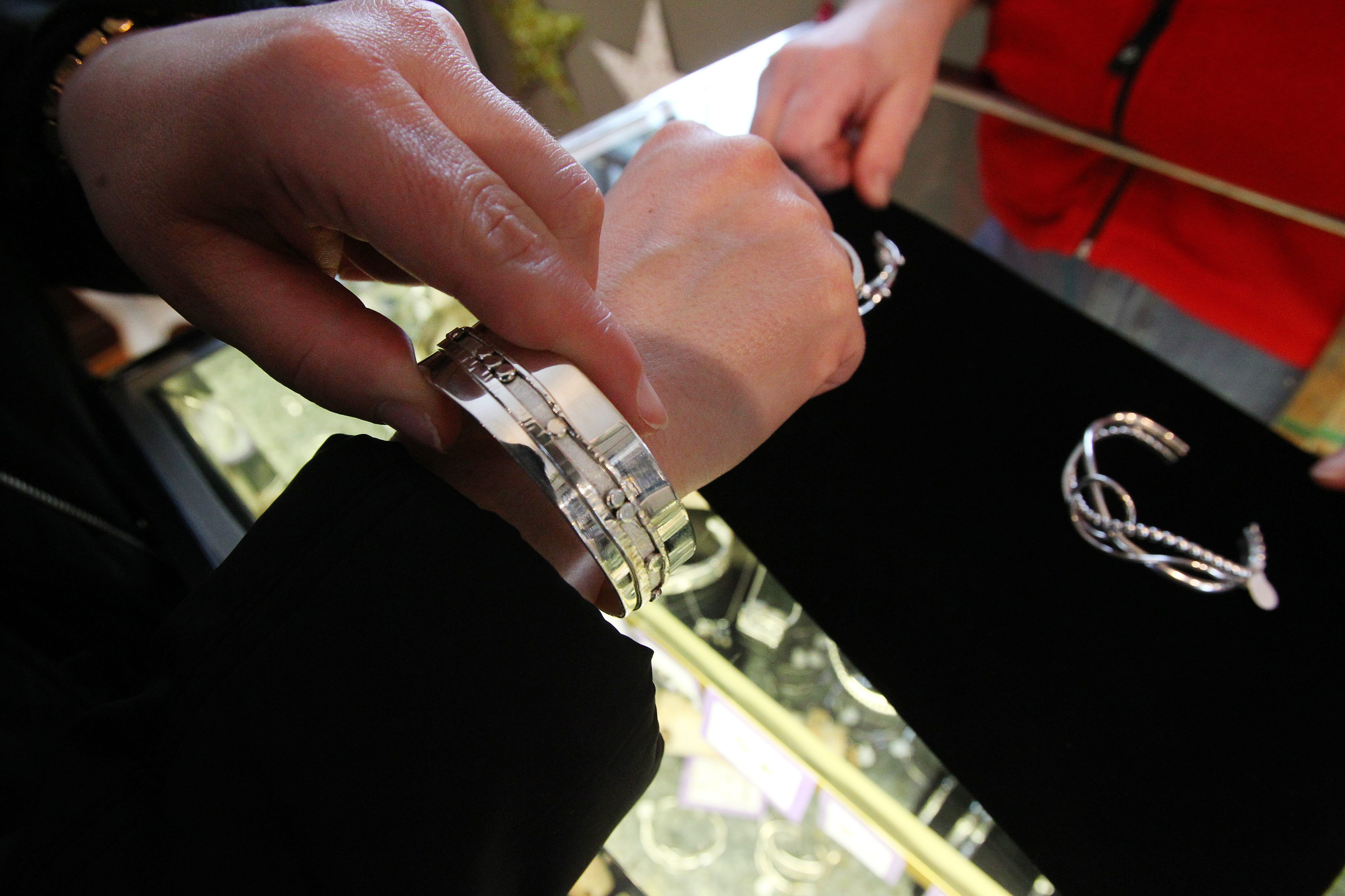 A shopper tries on a silver bracelet at the West End Gallery in East Aurora Friday, December 13, 2013.  (Mark Mulville/Buffalo News)