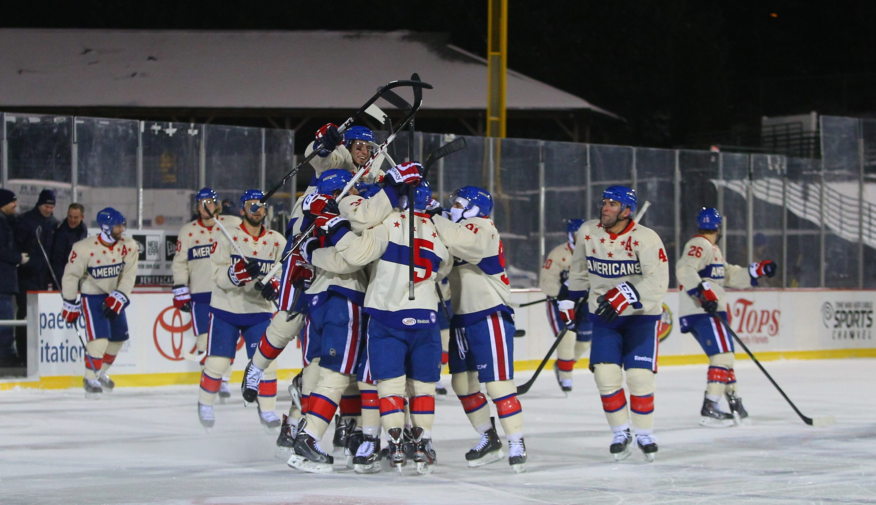 A pack of Rochester Americans celebrates Friday's shootout win over the Lake Erie Monsters at Frontier Field. Matt Ellis scored the winner.