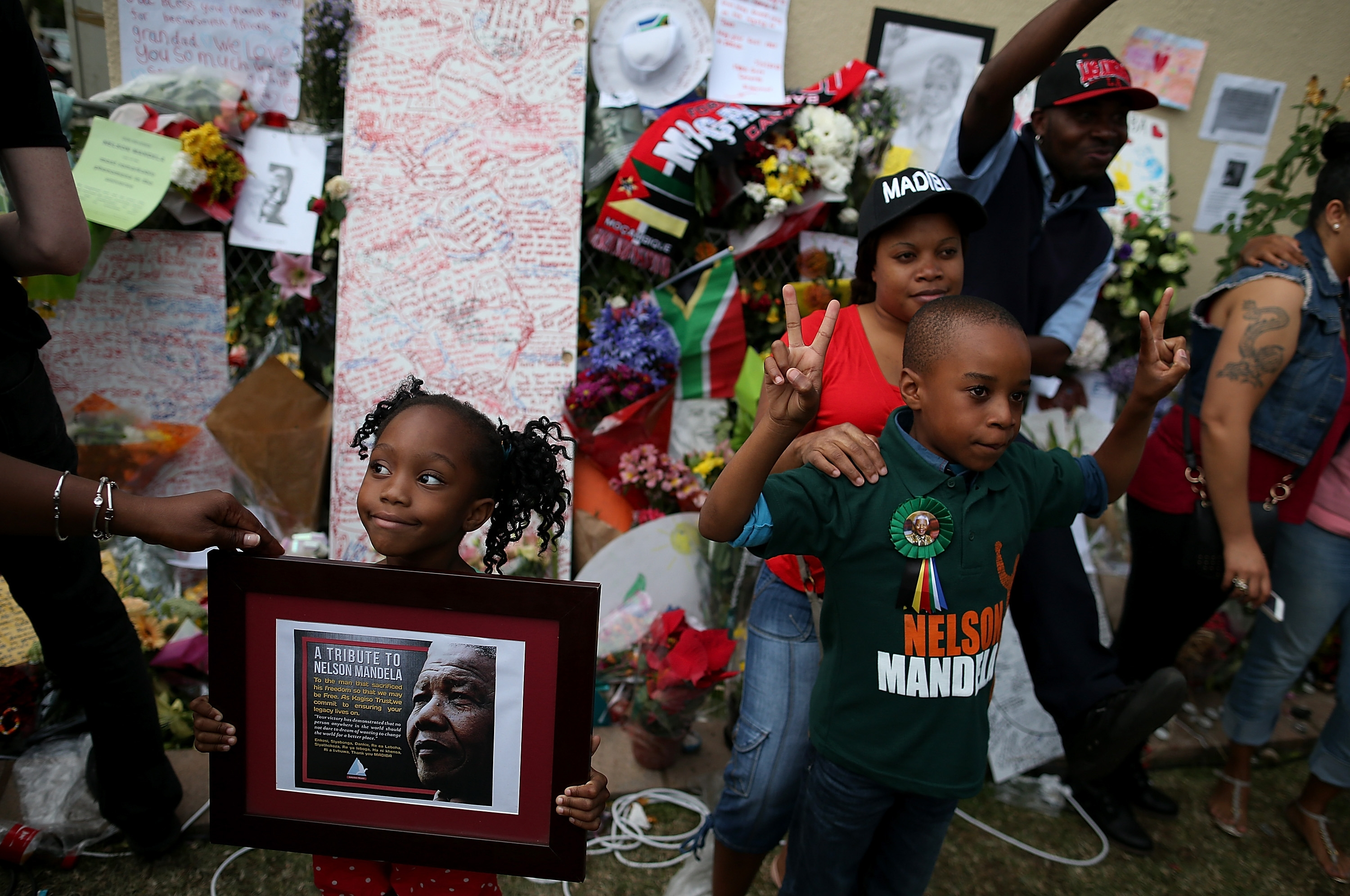 In Johannesburg, South Africa, people gather Saturday in front of a shrine of flowers, cards and candles to celebrate the life of Nelson Mandela outside his home. Mandela died Thursday at age 95.