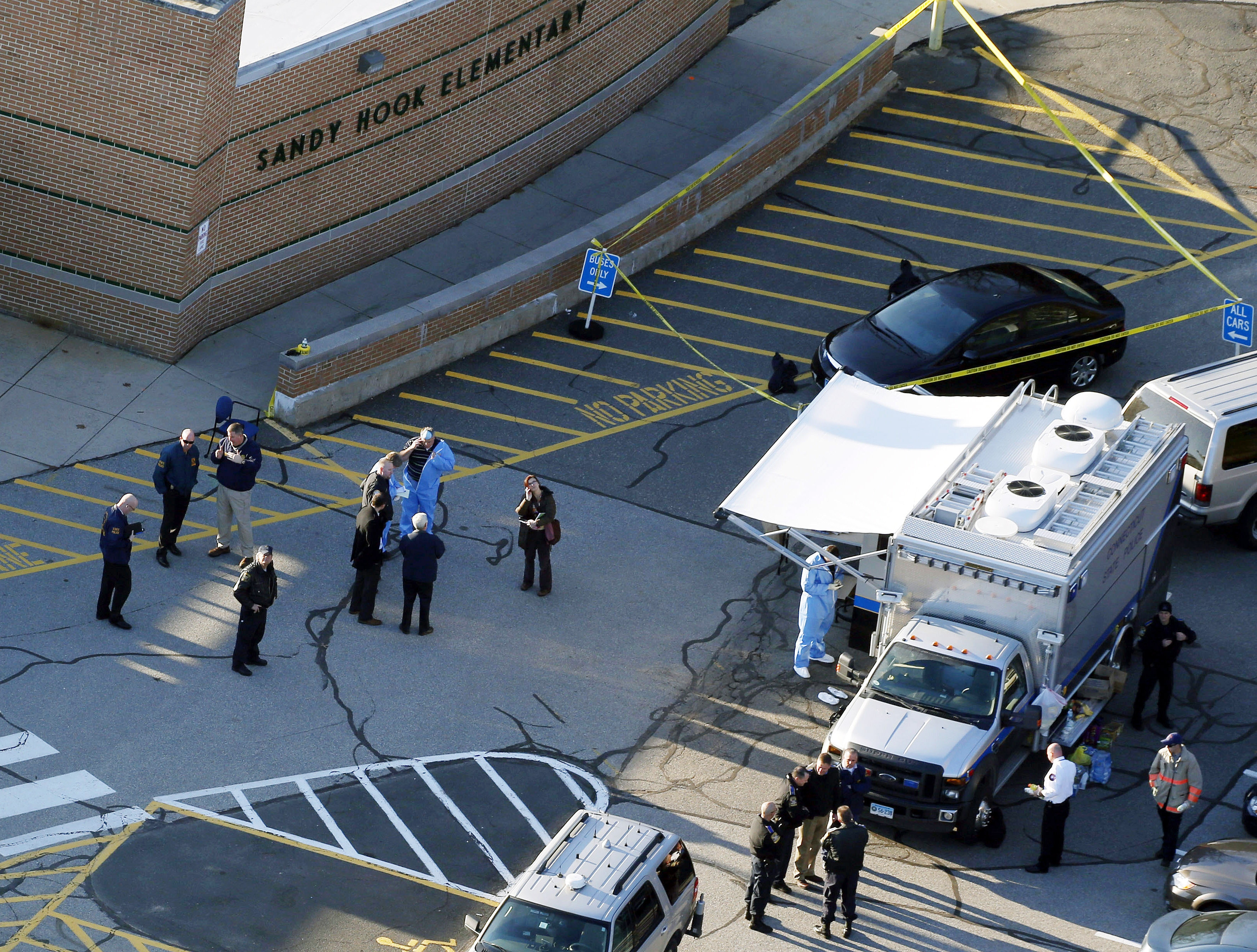 Under new guidelines, paramedics responding to mass attacks such as the one at Sandy Hook Elementary School last year, above, should move onto the scene more quickly than they've been advised to in the past.