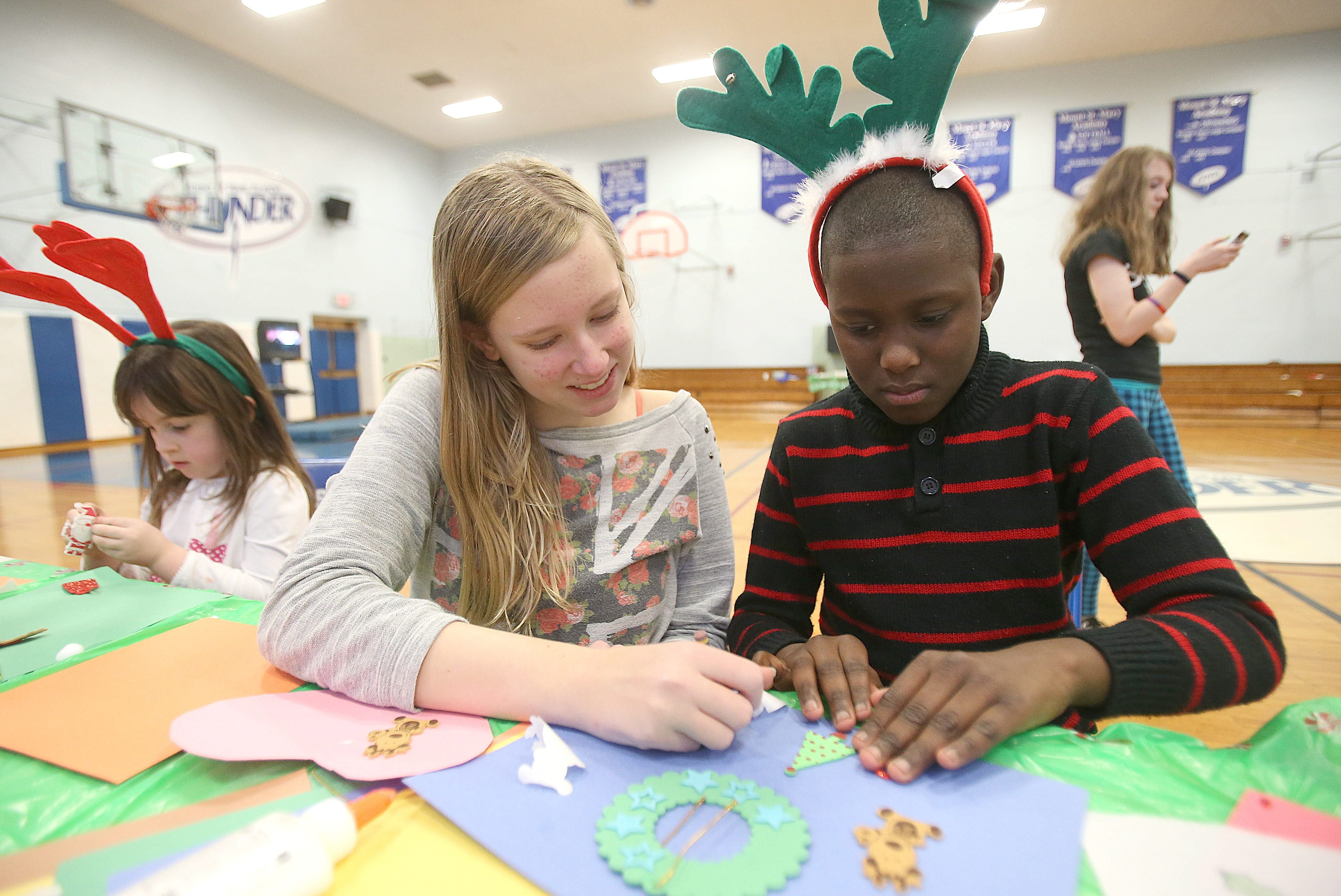 Mount St. Mary's ninth-grader Chloe Matecki checks the progress of 10-year-old Calvin Dyson's ornament during the Holiday Drop and Shop event at the school on Sunday. Proceeds from the program benefited the school's Alumni Scholarship.
